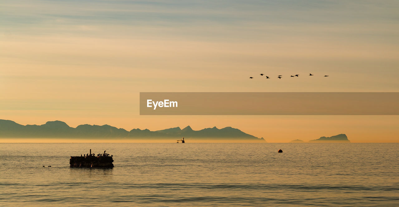Silhouette of boat in sea against mountain in background