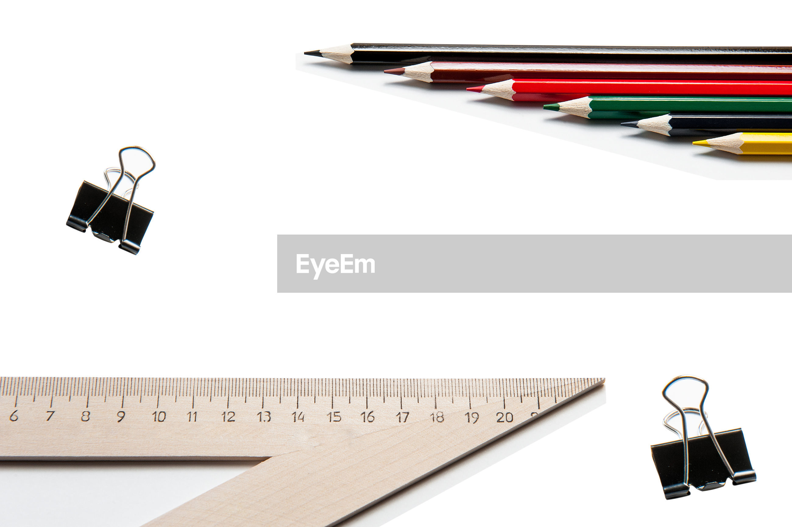 High angle view of colored pencils by paper clips and ruler against white background
