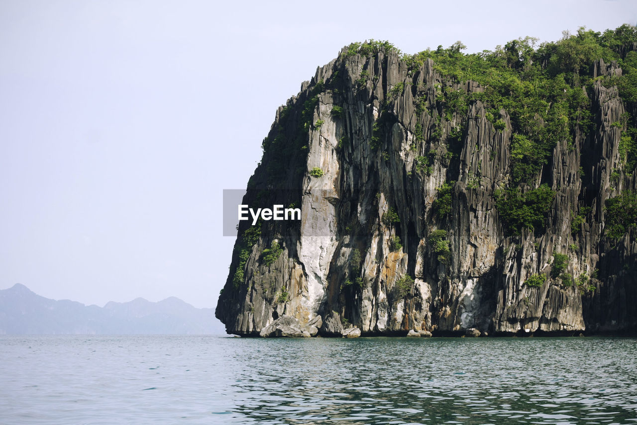 Low angle view of rock formations on sea against clear sky