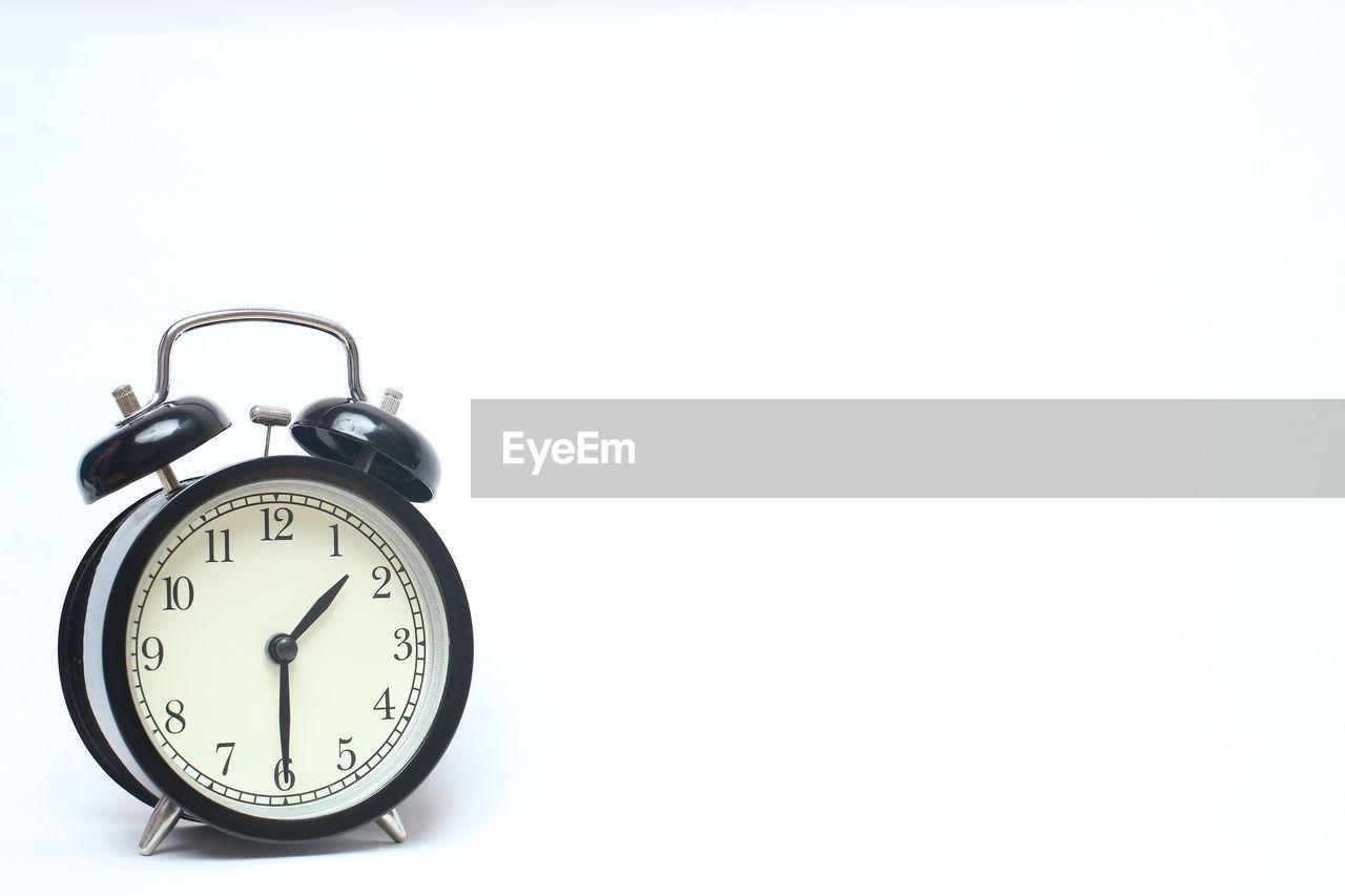 Close-up of alarm clock on white background