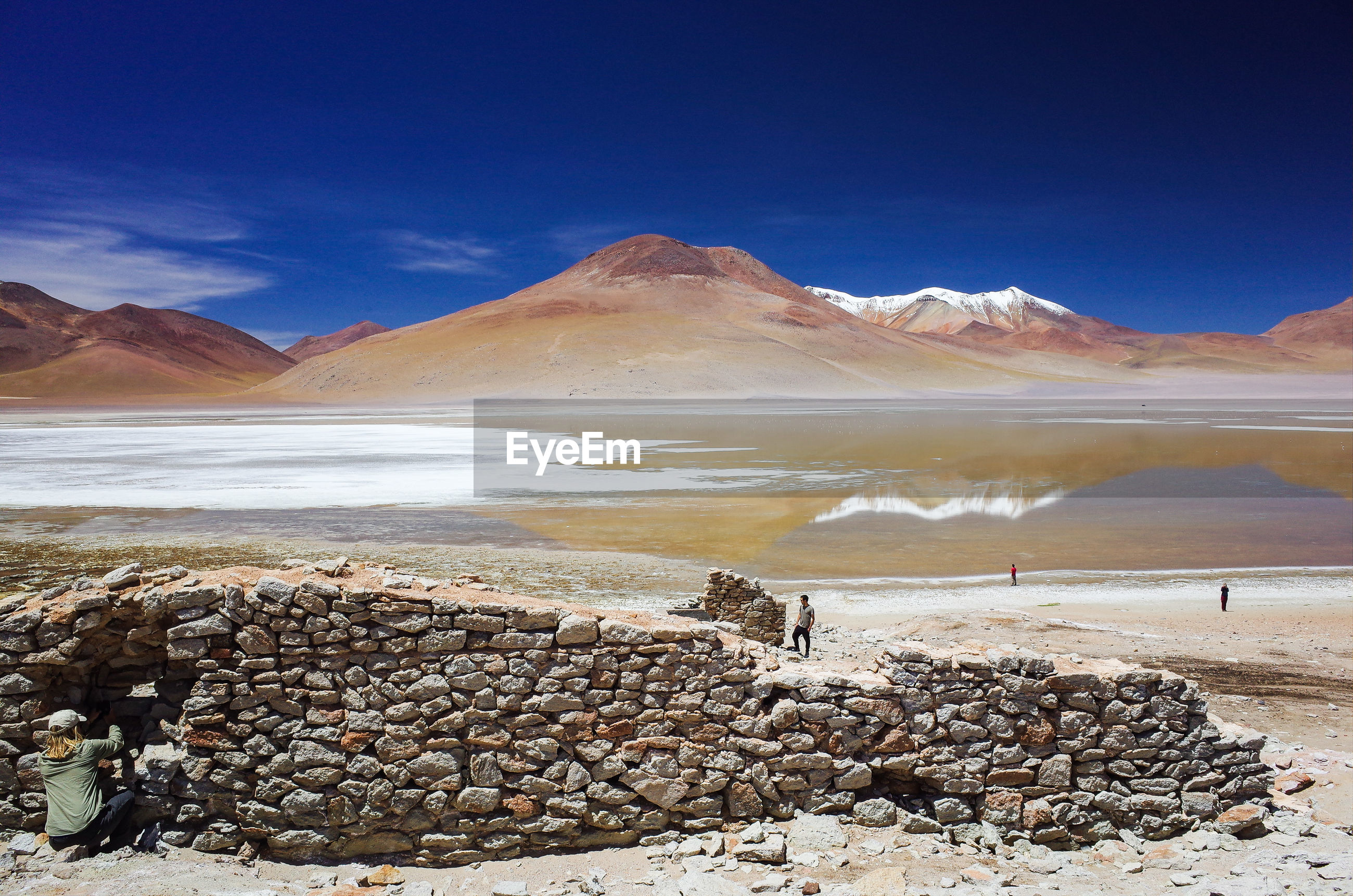 sky, mountain, beauty in nature, scenics - nature, water, nature, solid, tranquil scene, rock, day, land, tranquility, mountain range, blue, non-urban scene, cloud - sky, idyllic, beach, no people, outdoors, stone wall, snowcapped mountain