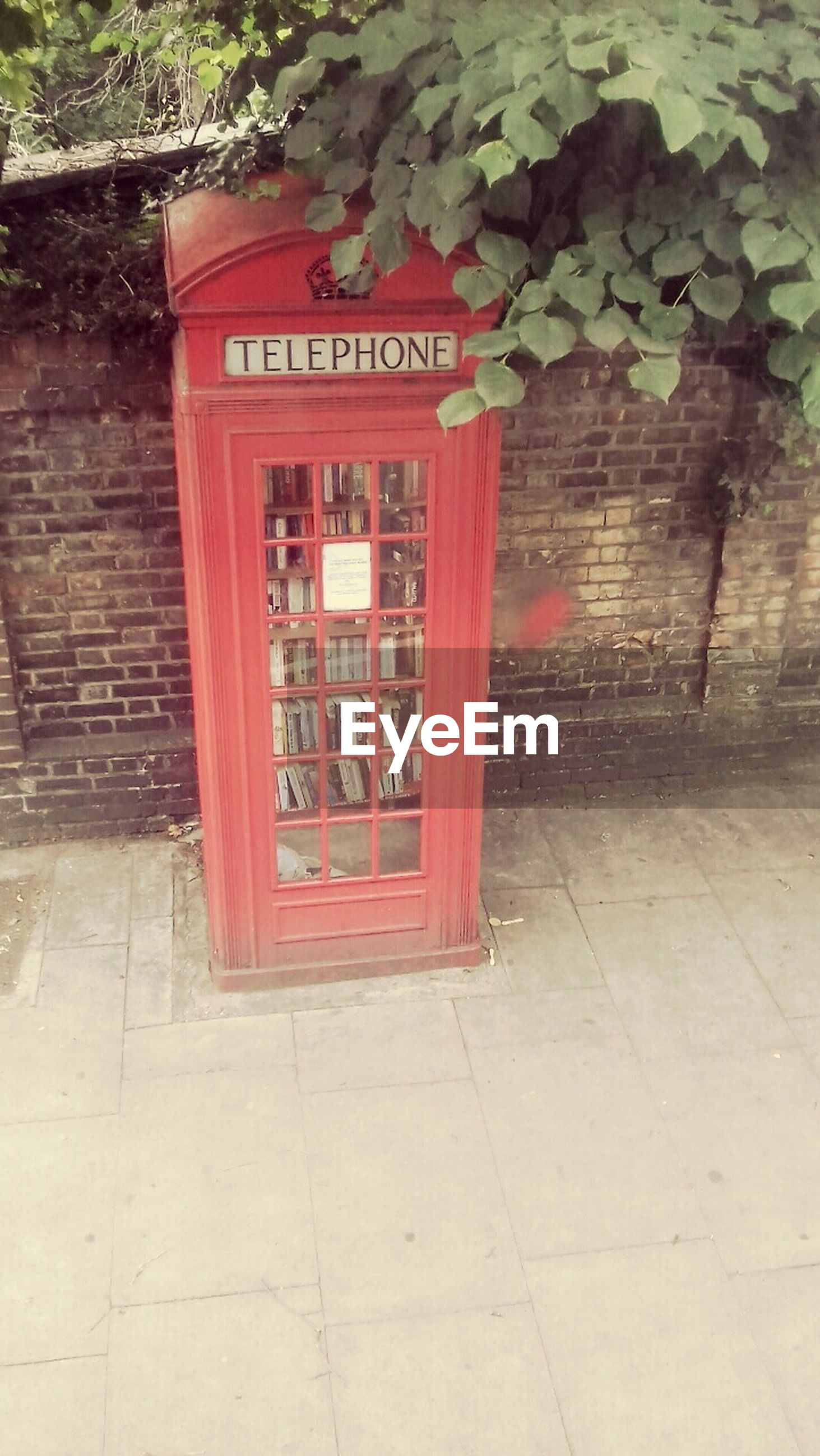 communication, red, text, western script, telephone booth, pay phone, day, architecture, built structure, outdoors, sidewalk, building exterior, no people, telephone, convenience