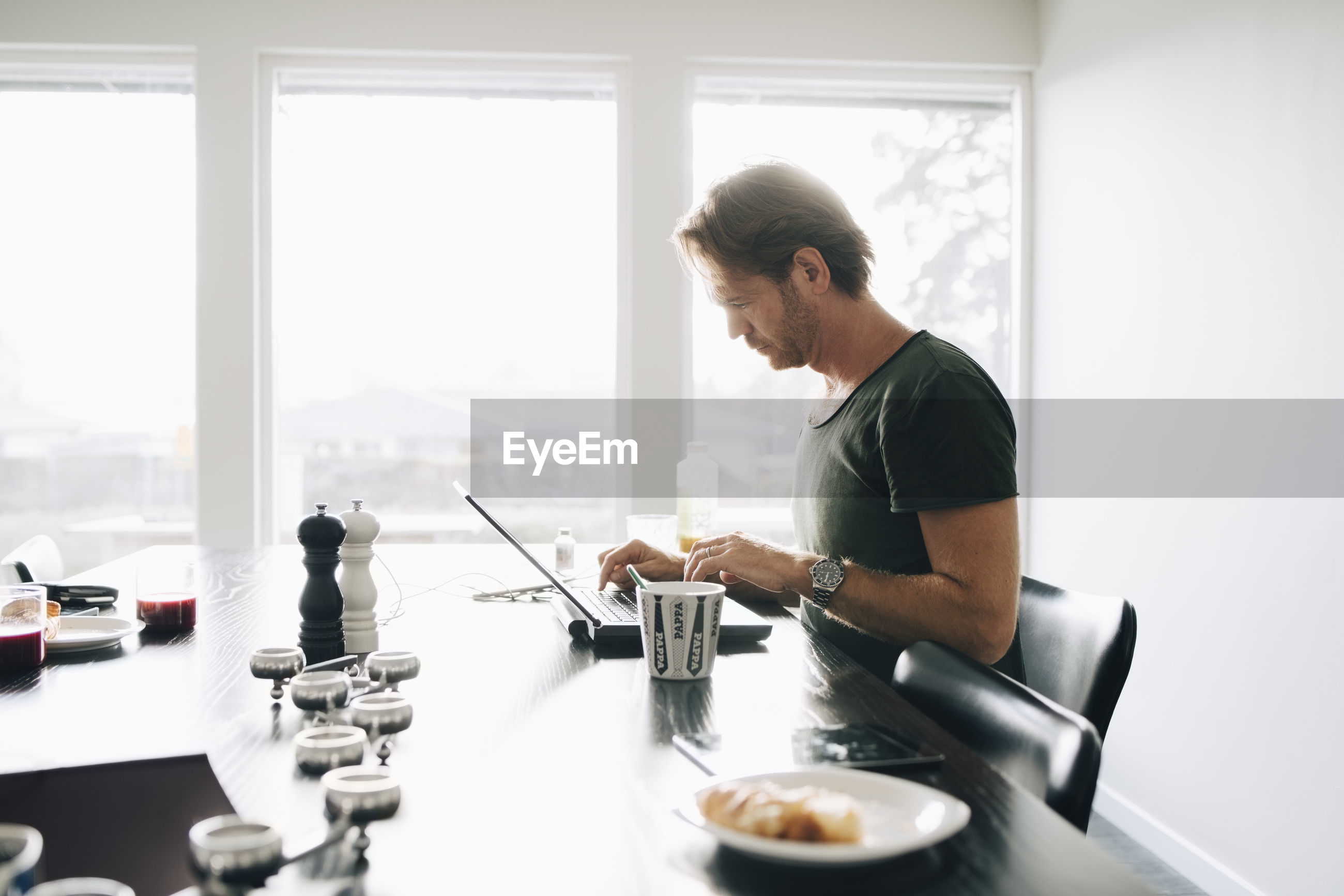 Side view of mature man sitting at dining table using laptop against window