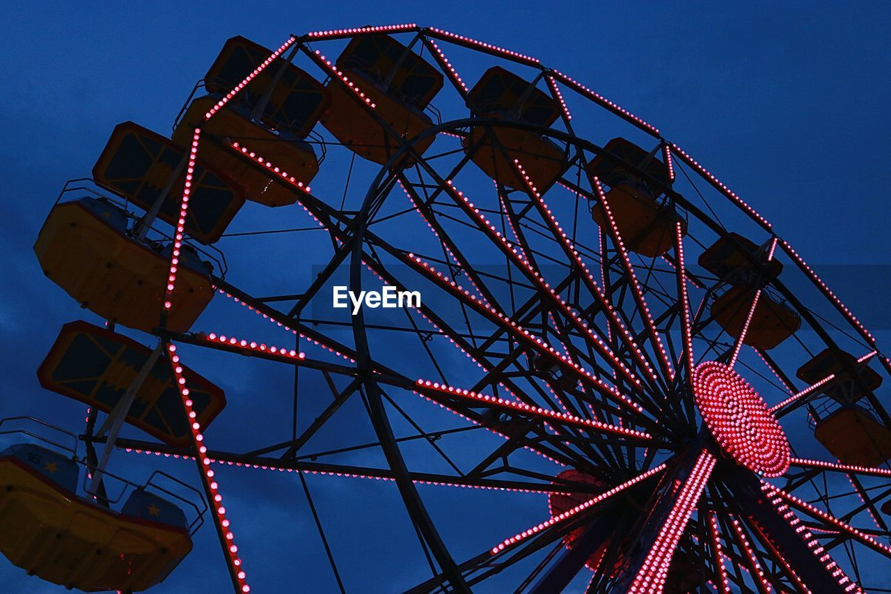 Low angle view of illuminated ferris wheel against blue sky