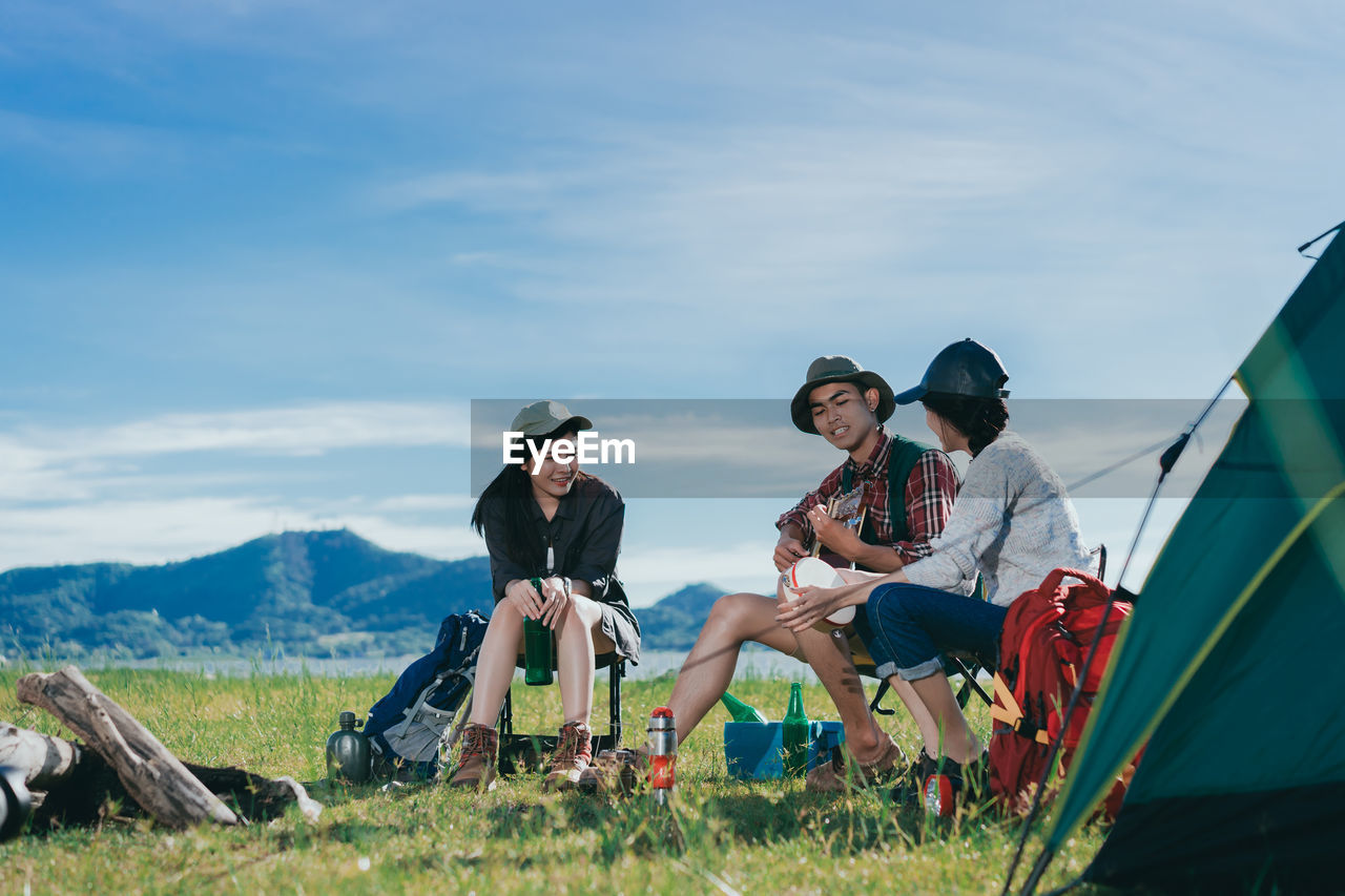 Friends Looking At Young Man Playing Guitar While Sitting On Chairs Against Sky