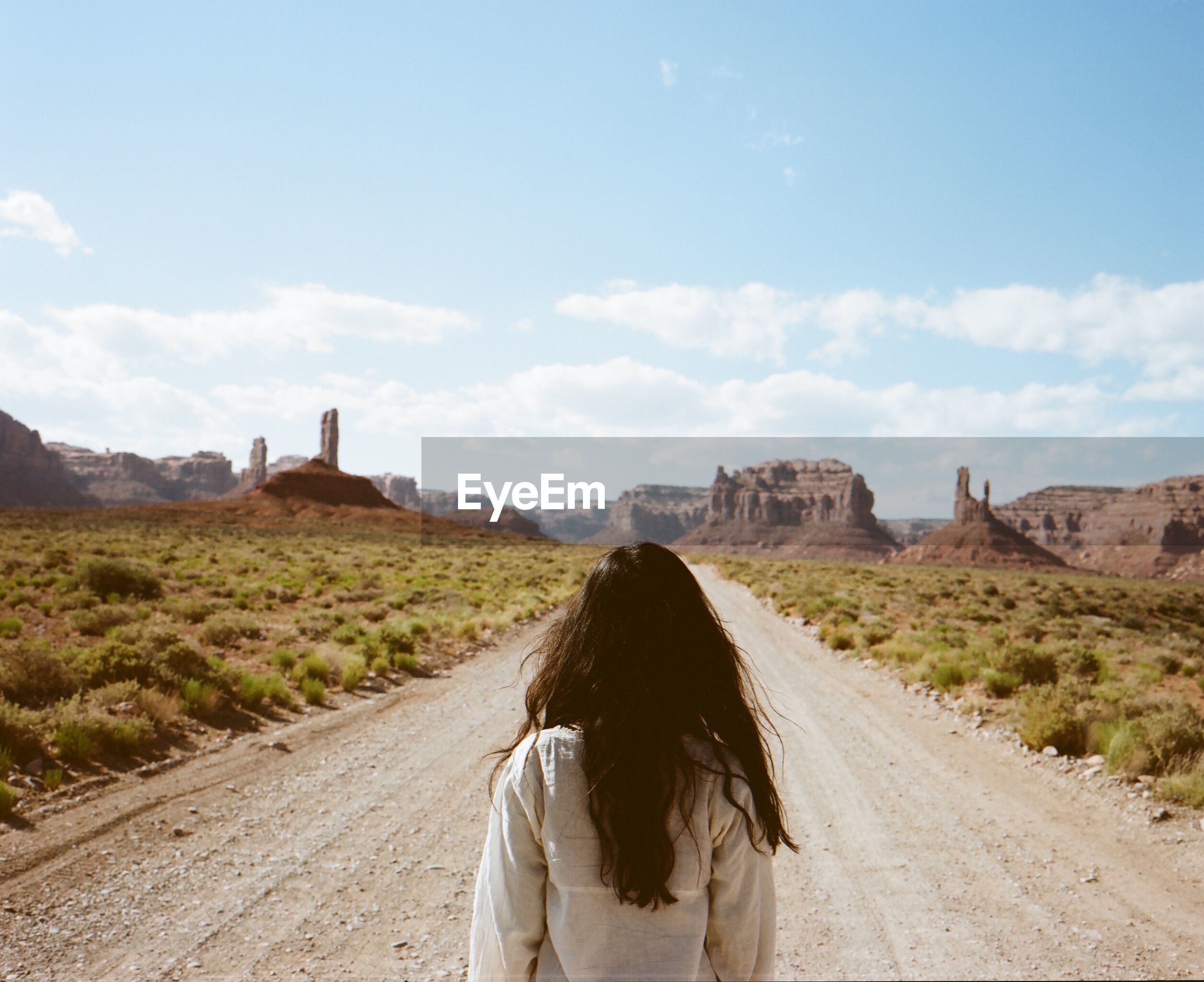 Rear view of woman standing on dirt road in arid landscape against sky