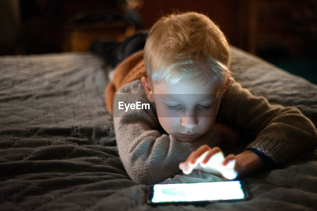 Boy Using Smart Phone While Lying On Bed At Home