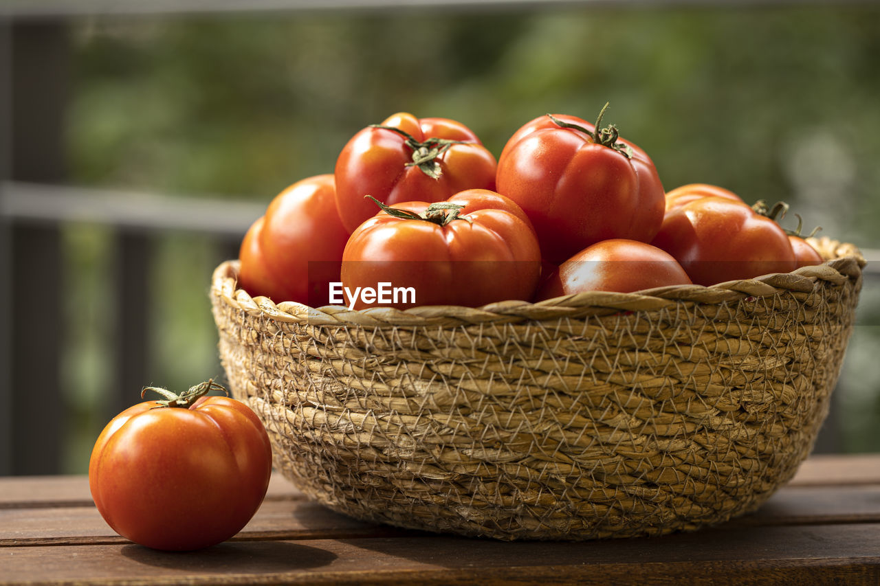 CLOSE-UP OF TOMATOES ON WOOD
