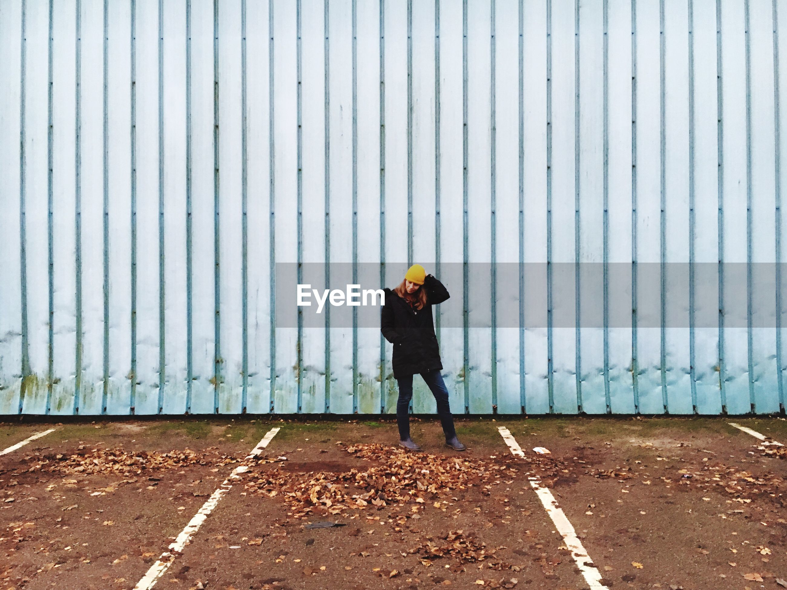 Woman standing by dry leaves fallen at parking lot against corrugated fence