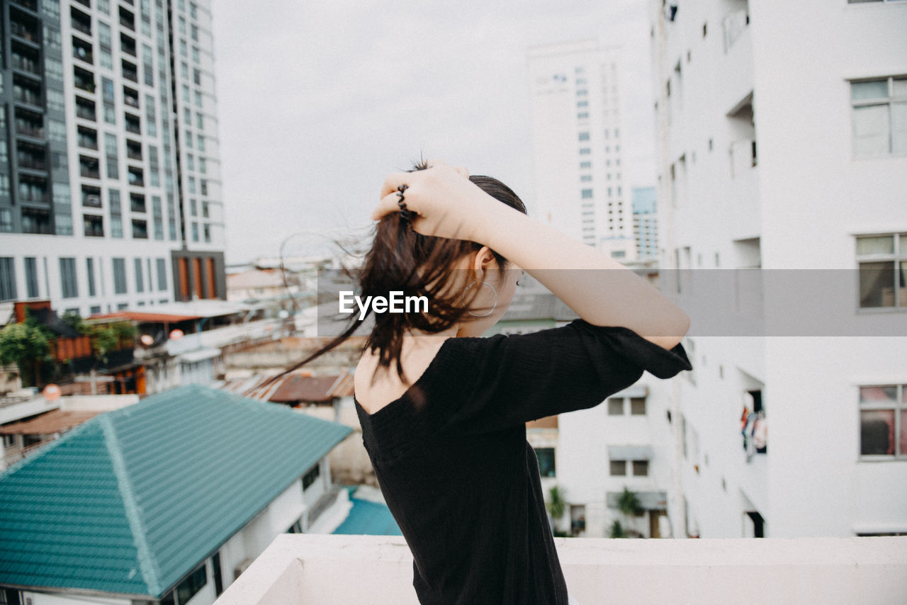Side view of young woman standing on building terrace against sky