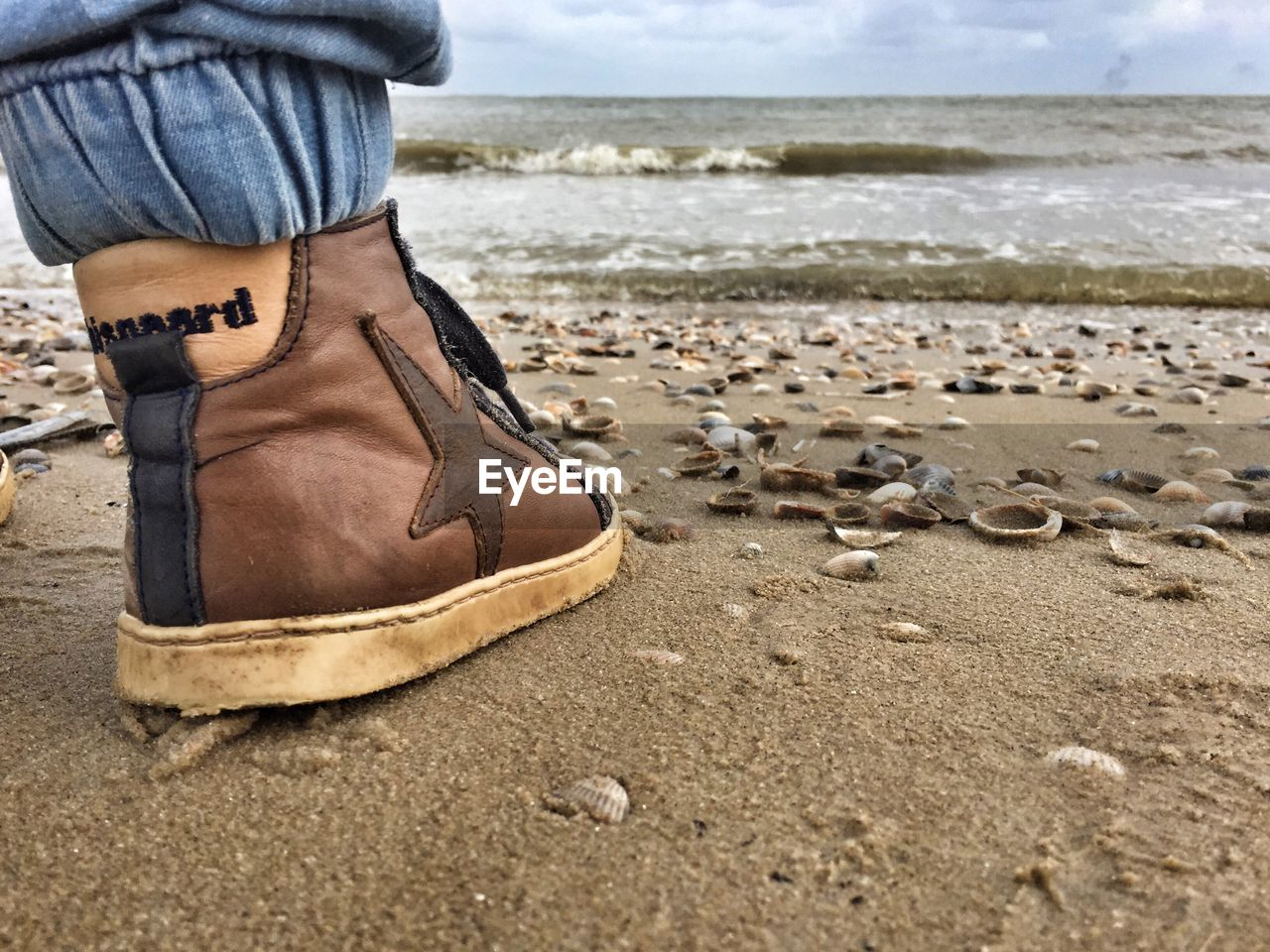 low section, shoe, water, sea, one person, human leg, human body part, land, beach, sky, body part, horizon, day, leisure activity, nature, horizon over water, lifestyles, human foot, outdoors, human limb, jeans