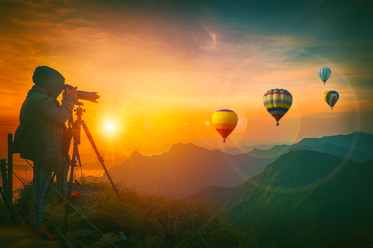 Woman photographing hot air balloons against sky during sunset