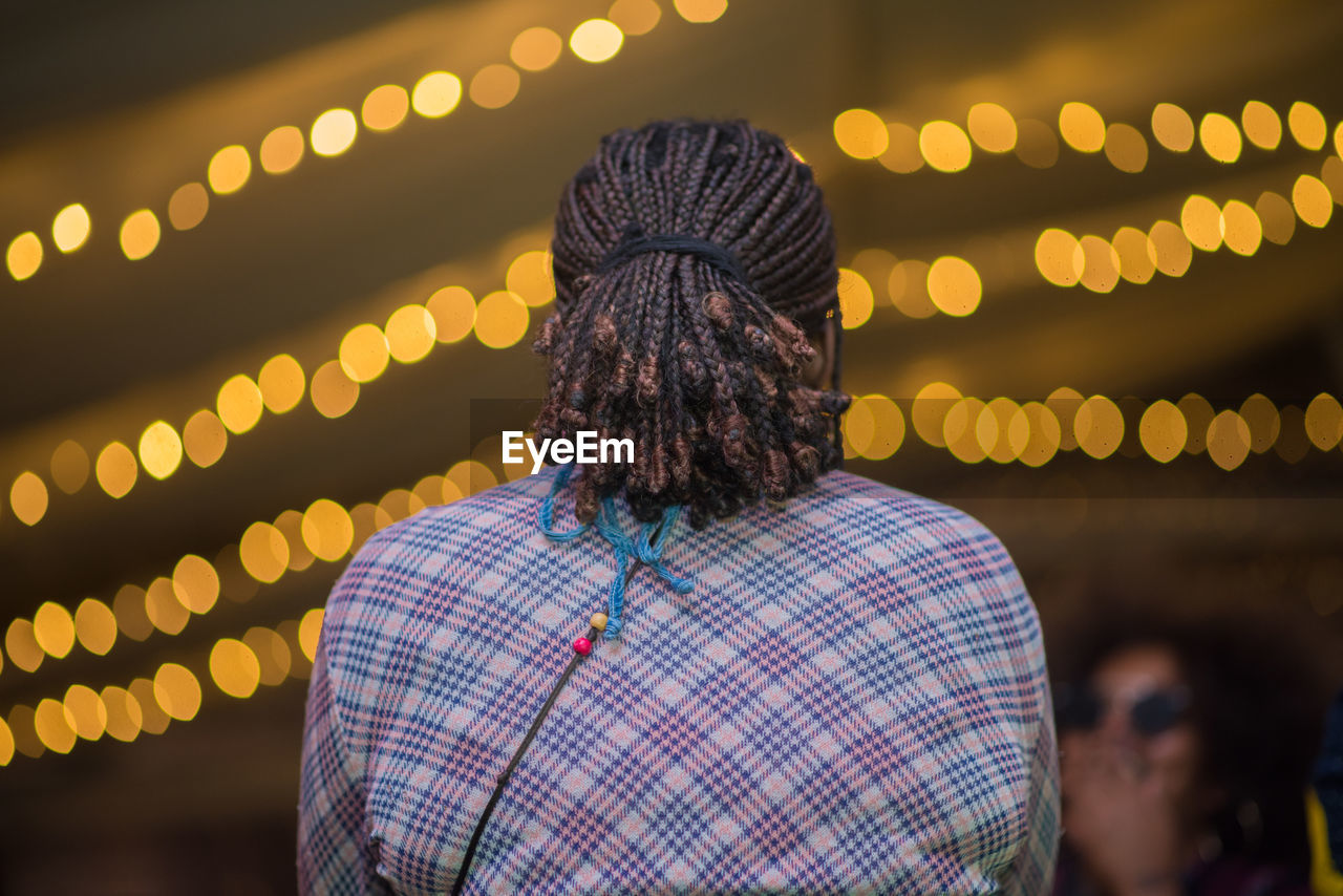 Rear view of woman with dreadlocks against lens flare at night
