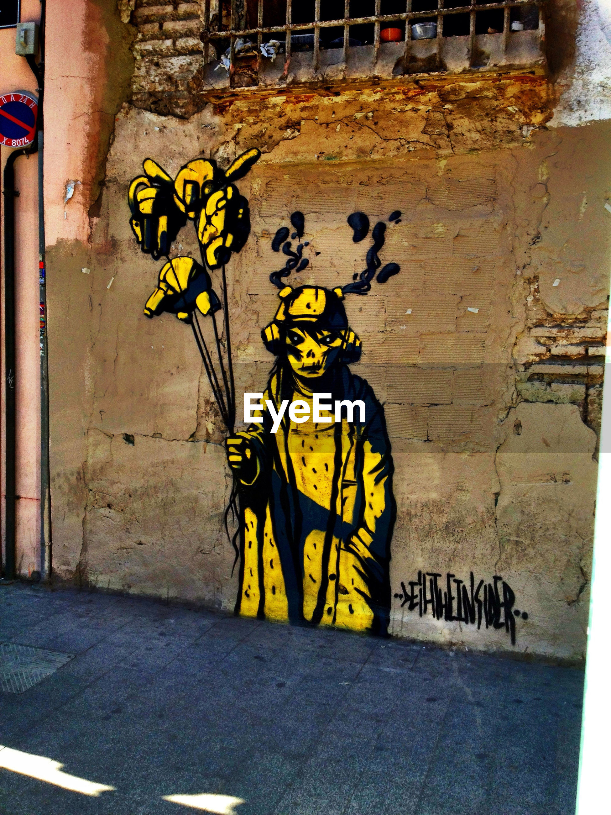 graffiti, text, wall - building feature, art, built structure, architecture, creativity, western script, yellow, art and craft, building exterior, street art, wall, street, sidewalk, day, communication, outdoors, flower, plant