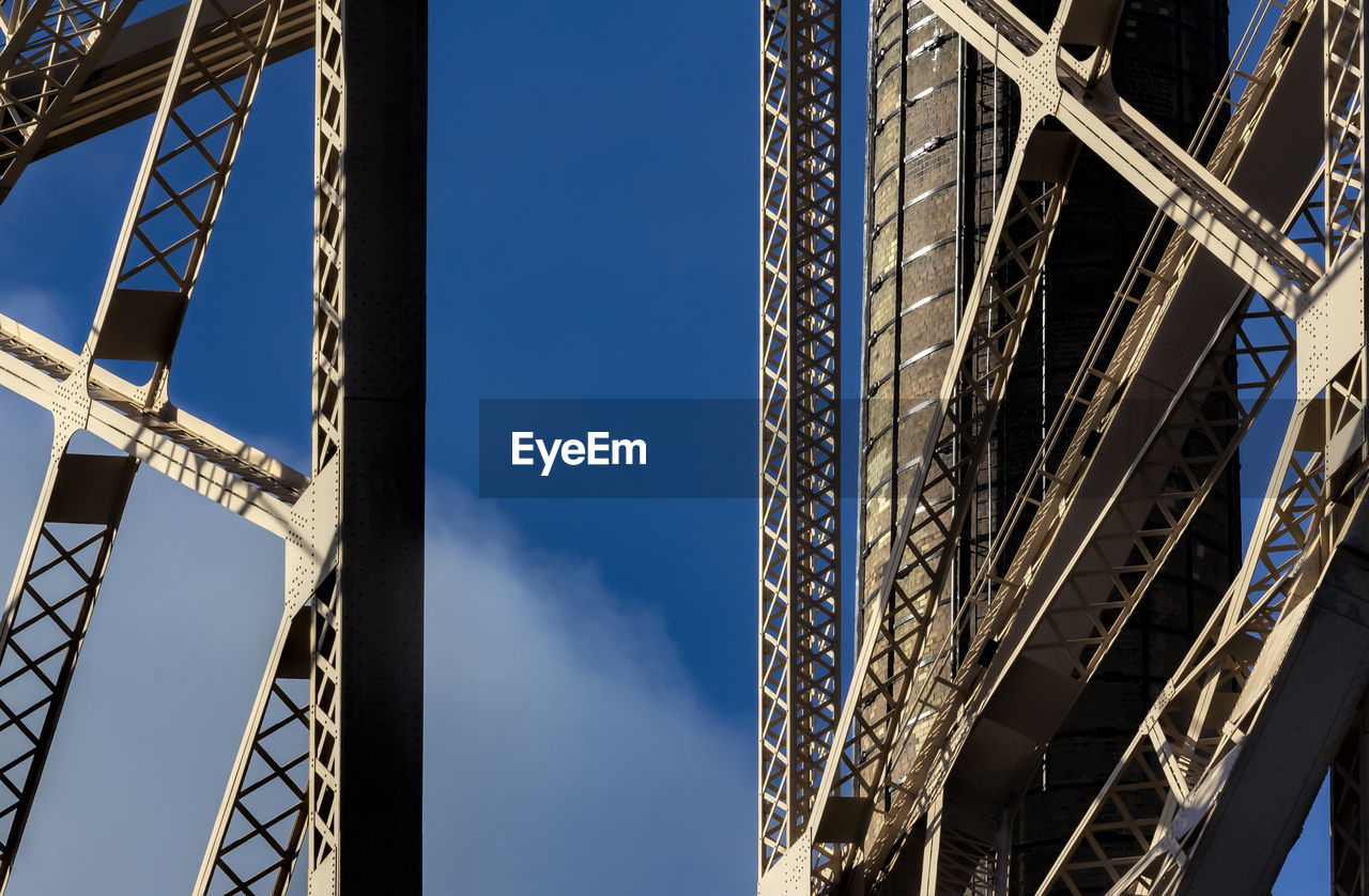 low angle view, sky, built structure, architecture, metal, nature, day, no people, blue, outdoors, sunlight, connection, bridge, bridge - man made structure, clear sky, strength, tall - high, pattern, travel destinations, girder, steel