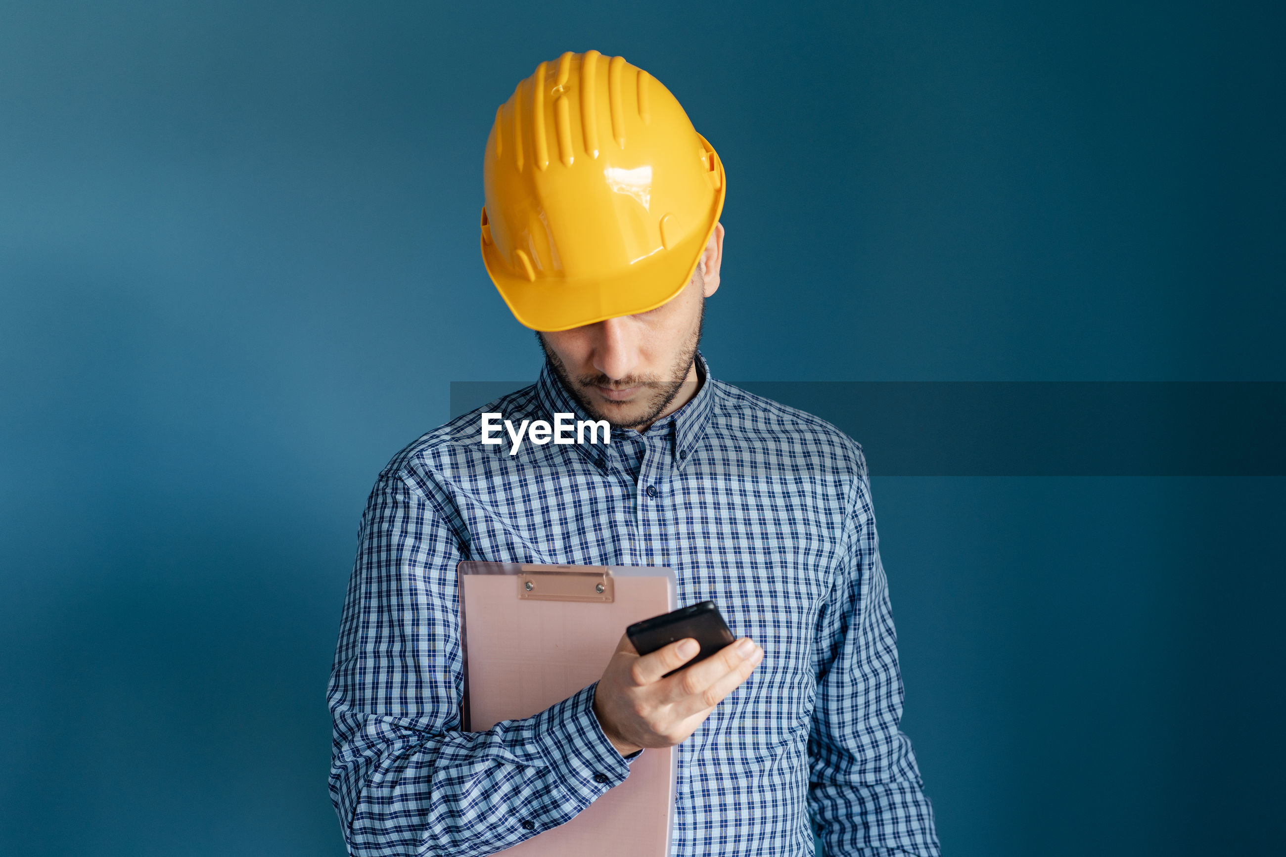 Engineer using mobile phone against blue background