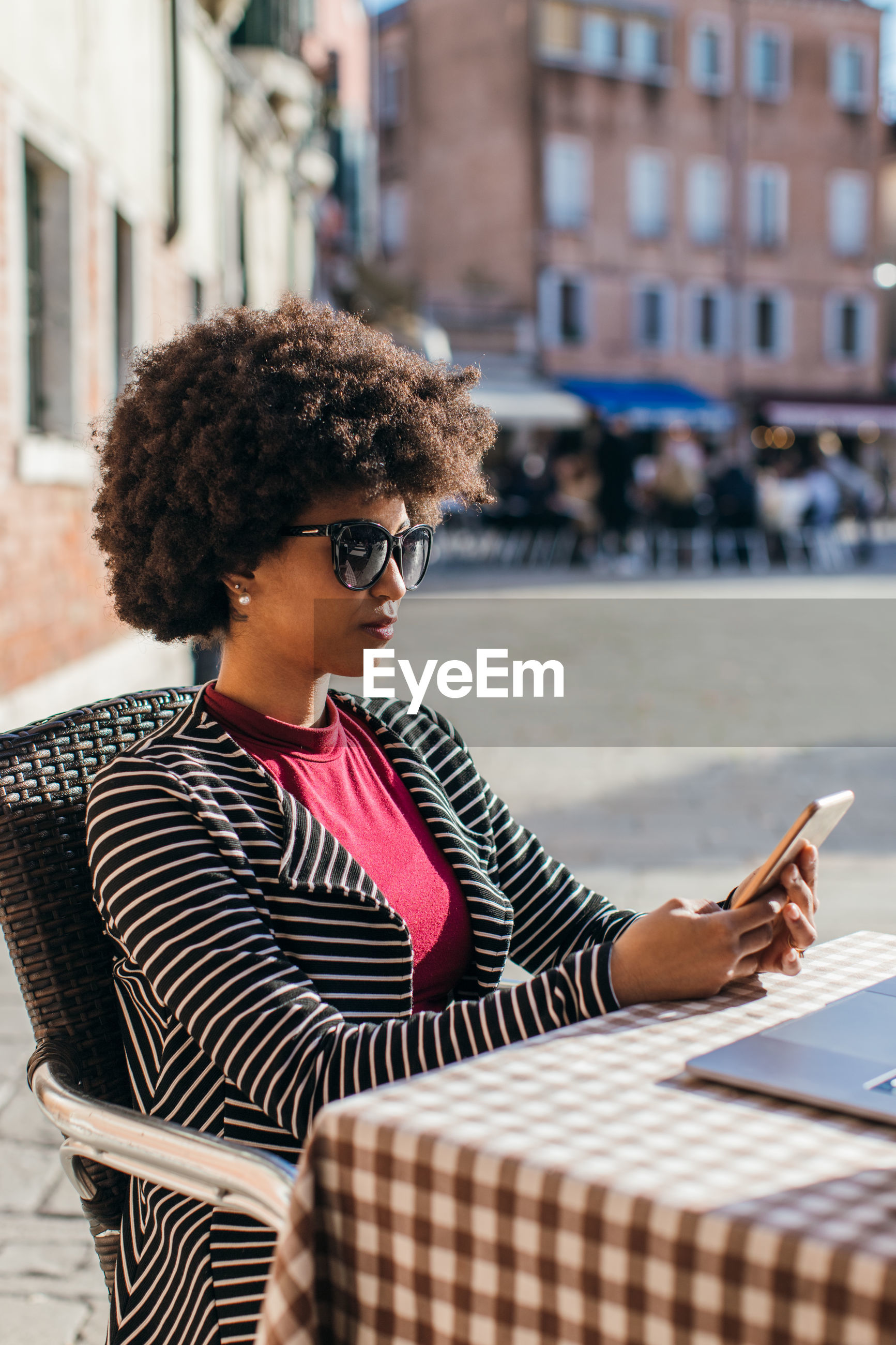 YOUNG WOMAN USING PHONE ON CITY
