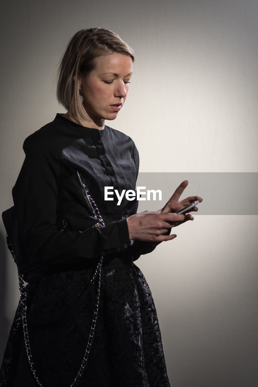 Woman Using Phone Against Gray Background