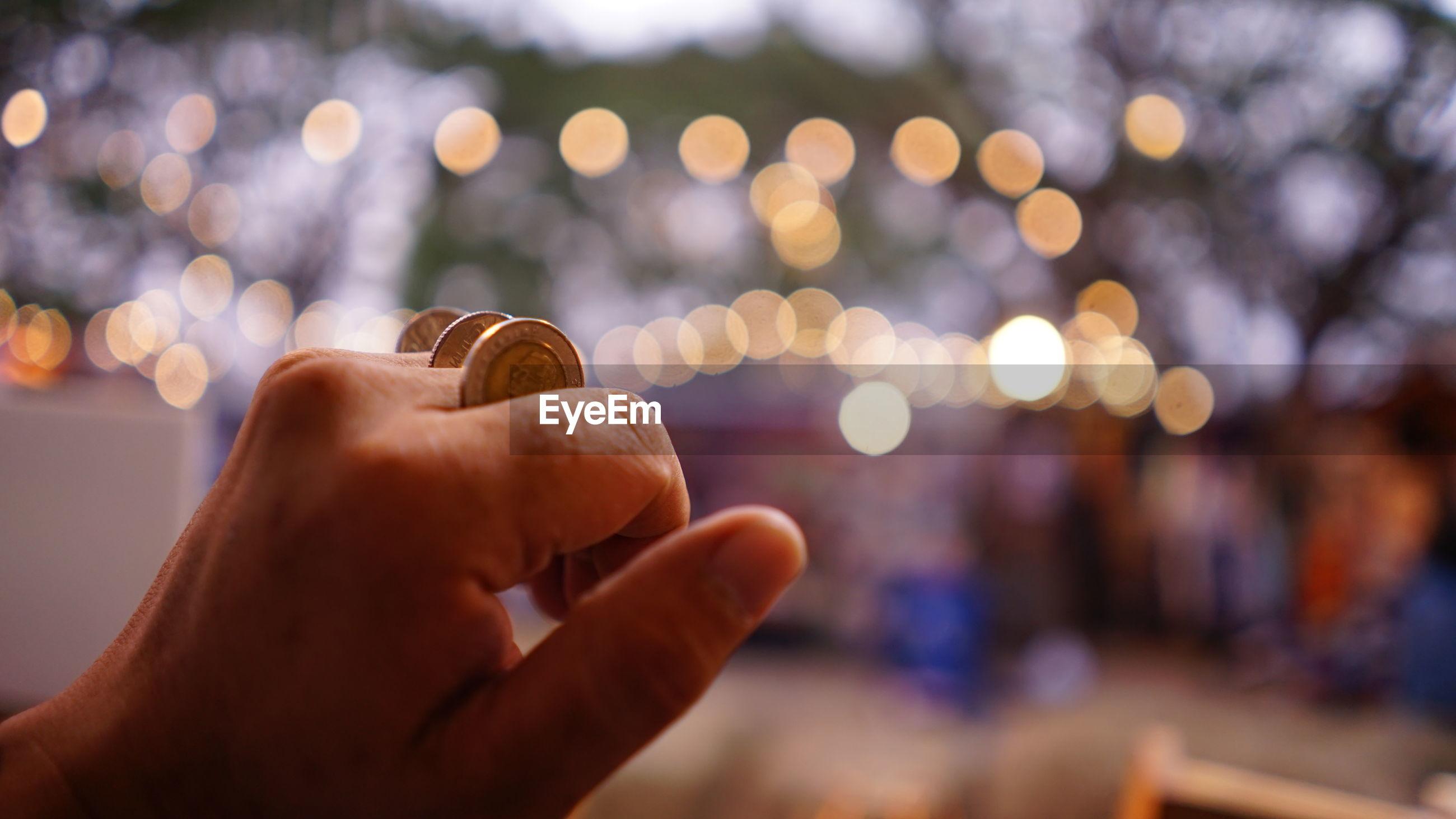 Close-up of hand holding illuminated blurred lights