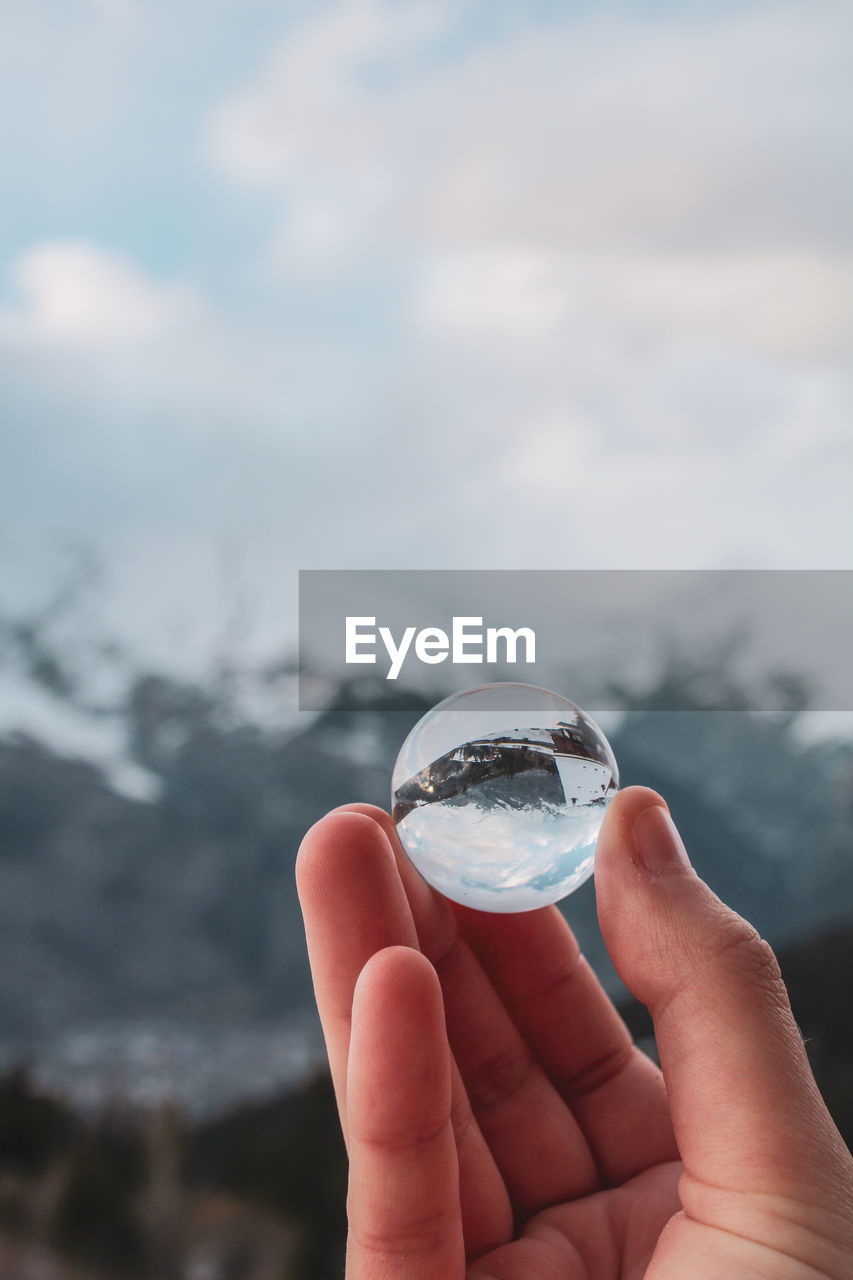 human hand, hand, holding, one person, human body part, focus on foreground, water, cloud - sky, nature, day, crystal ball, sphere, human finger, sky, finger, glass - material, transparent, body part, real people, outdoors, glass