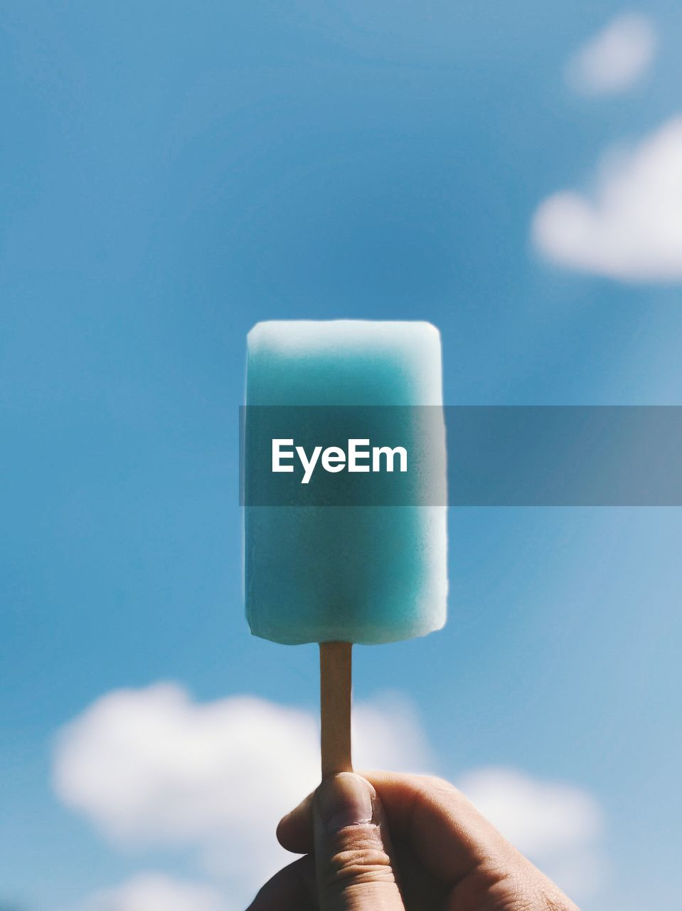 Close-Up Of Hand Holding Flavored Ice Against Blue Sky