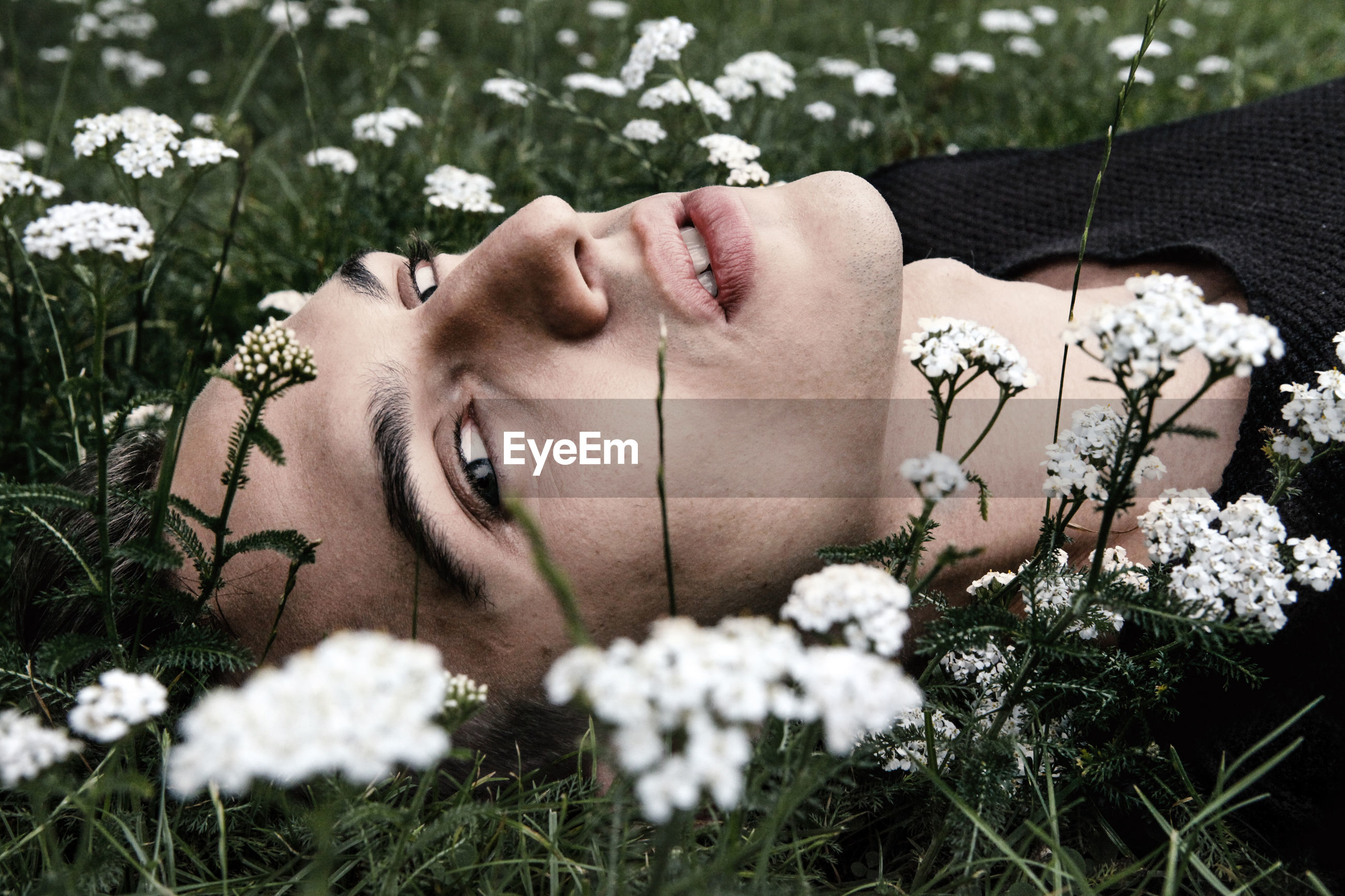 Young man lying down on grass
