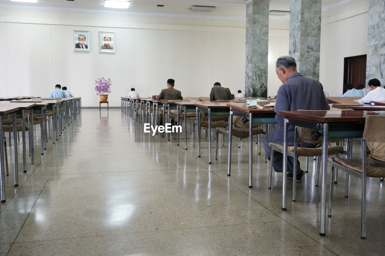Rear View Of People Studying On Benches At University Building