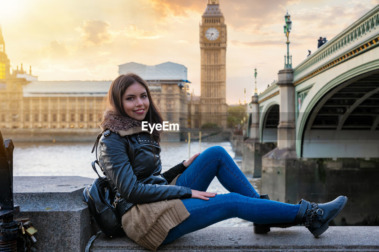 Portrait of smiling young woman sitting on railing against big ben during sunset