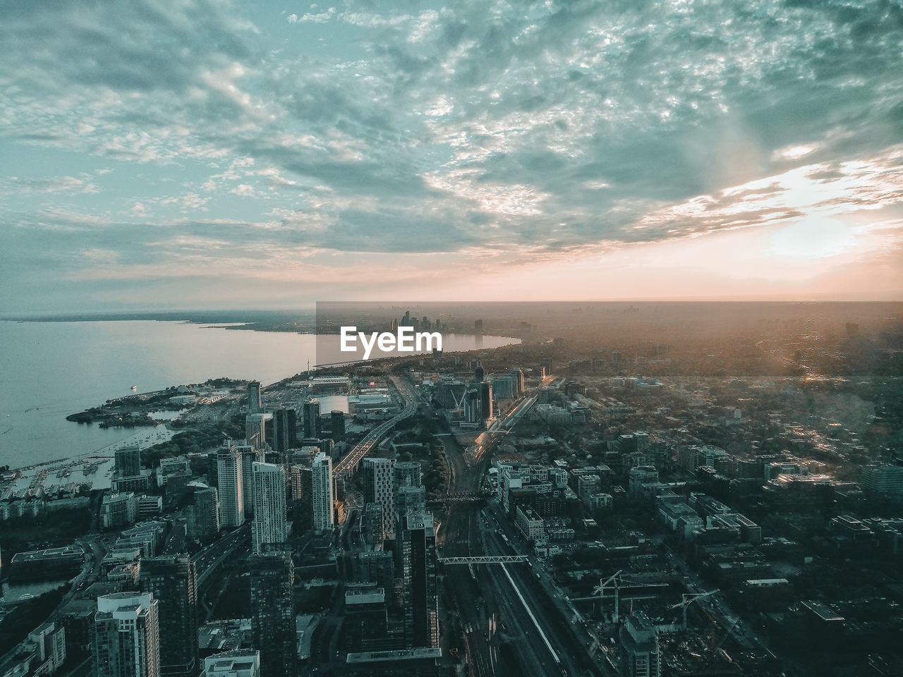 High angle view of cityscape and sea against sky during sunset
