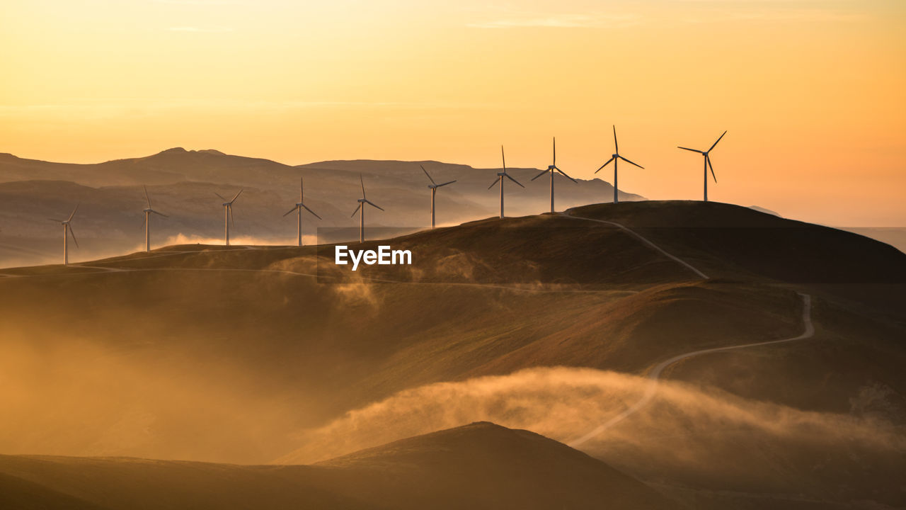 Low Angle View Of Silhouette Windmills On Mountain Against Sky During Sunset