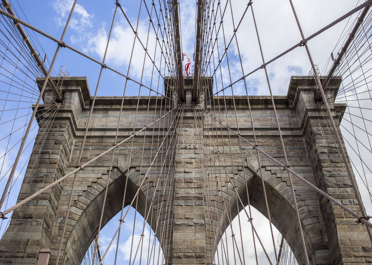 built structure, architecture, sky, bridge, low angle view, bridge - man made structure, transportation, arch, connection, travel, tourism, travel destinations, day, engineering, suspension bridge, cable, nature, flag, city, outdoors