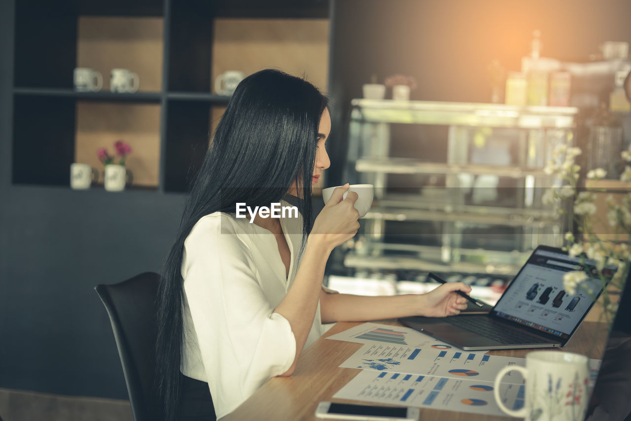 Businesswoman having coffee while using laptop at cafe