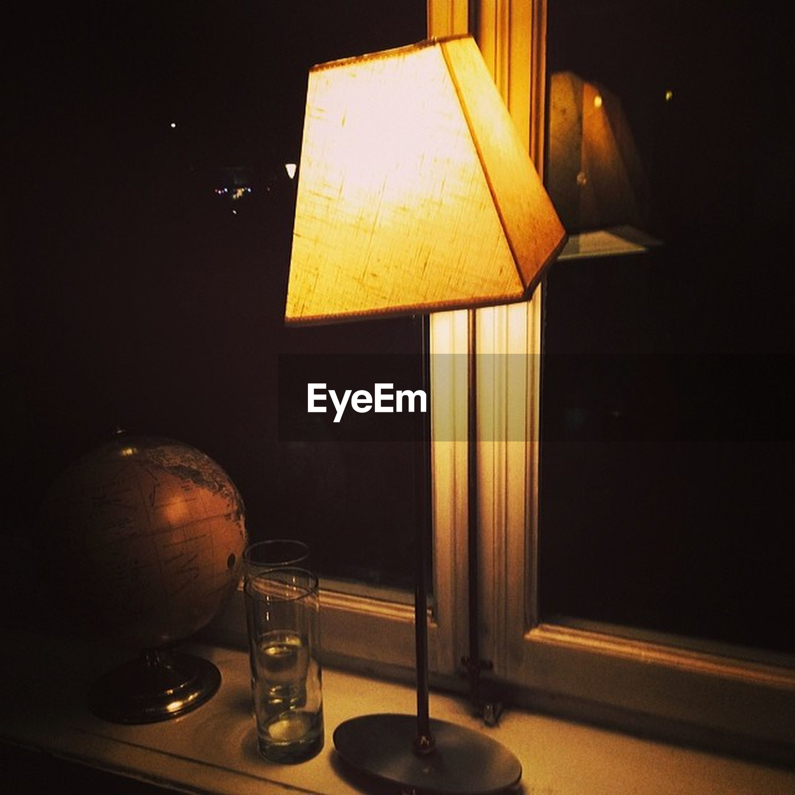 indoors, table, still life, close-up, yellow, illuminated, no people, night, glass - material, home interior, old-fashioned, paper, open, dark, text, single object, retro styled, high angle view, technology, communication