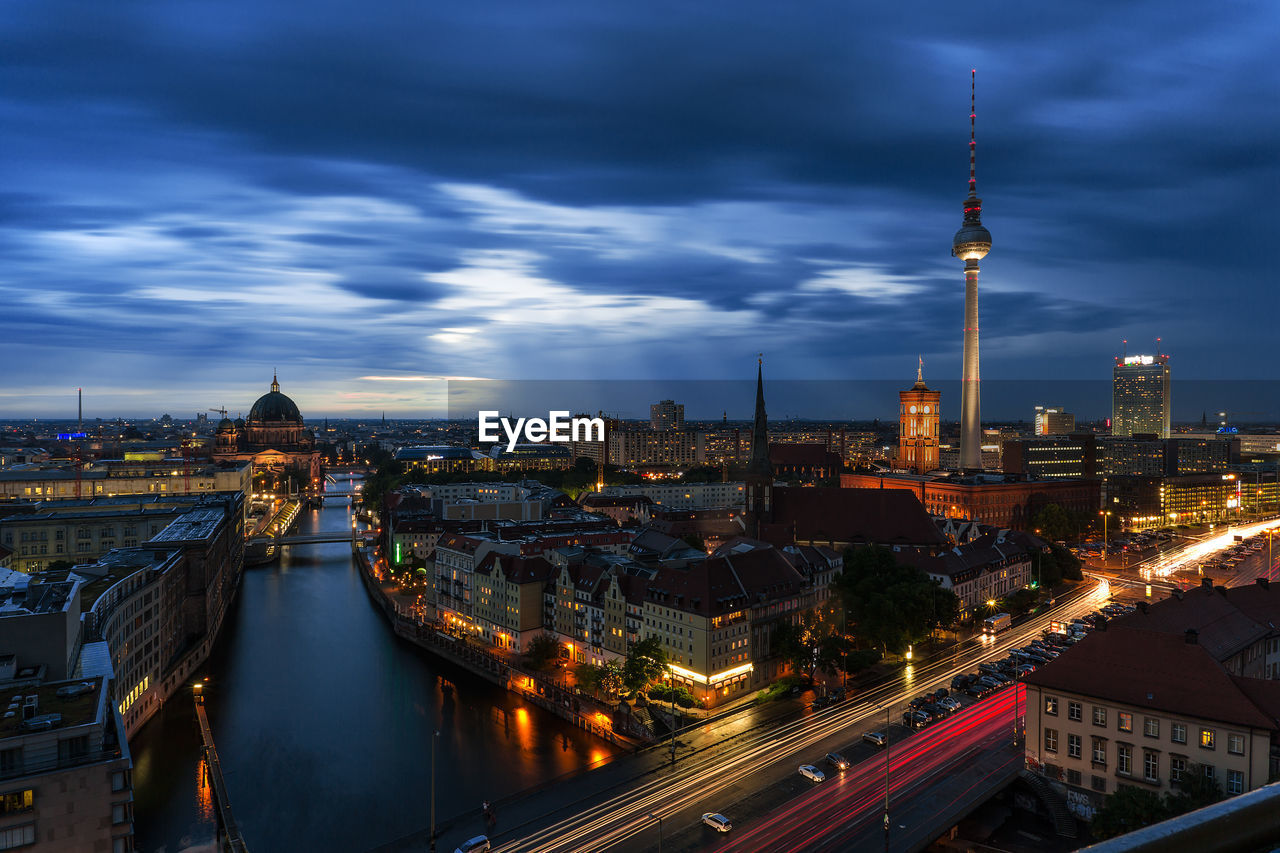 Distant View Of Illuminated Fernsehturm Against Cloudy Sky At Dusk