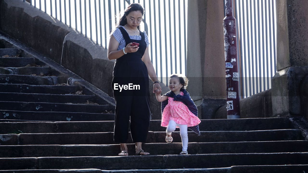 FULL LENGTH OF MOTHER AND DAUGHTER ON STAIRCASE