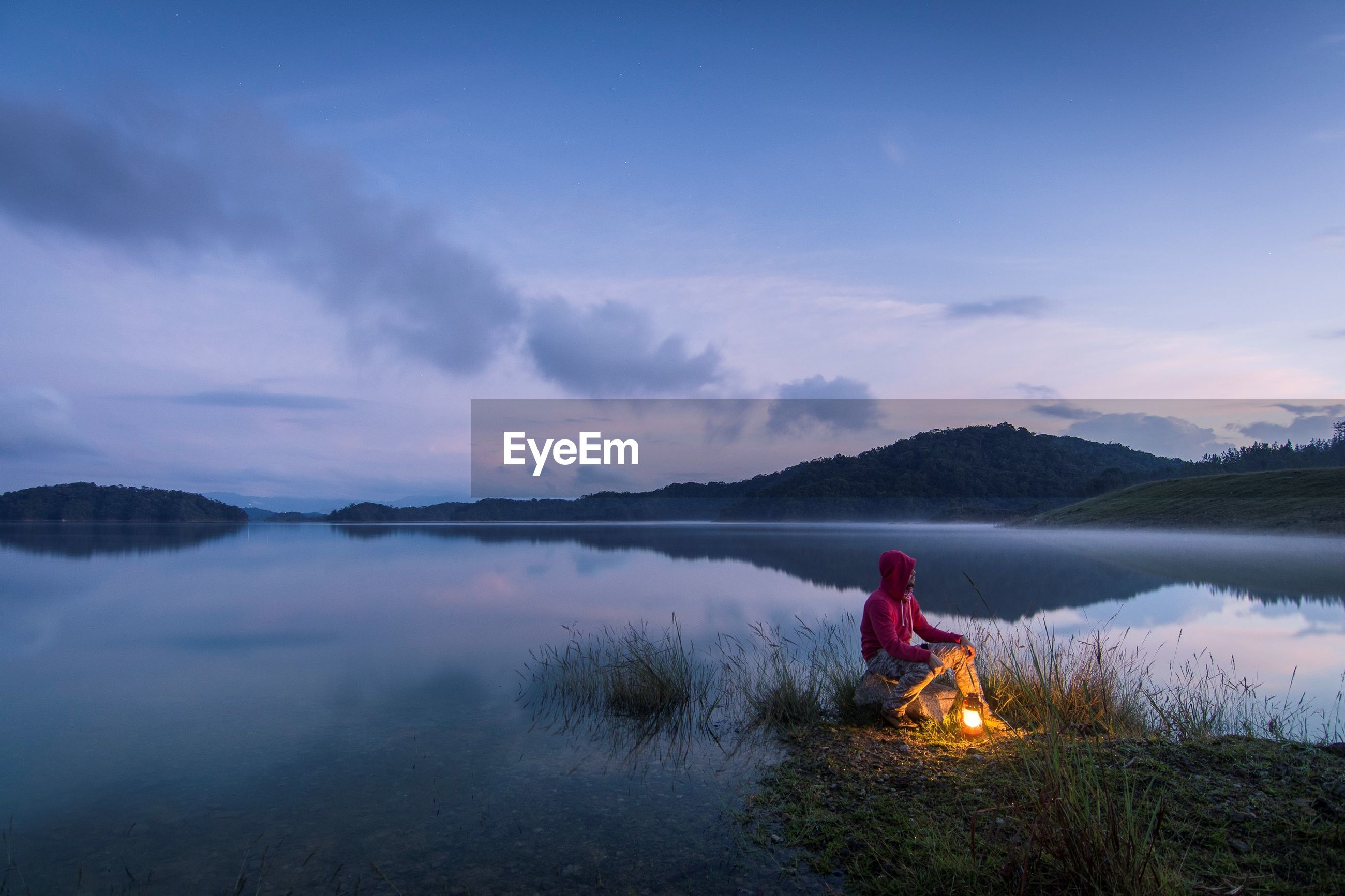Man sitting on lakeshore against sky