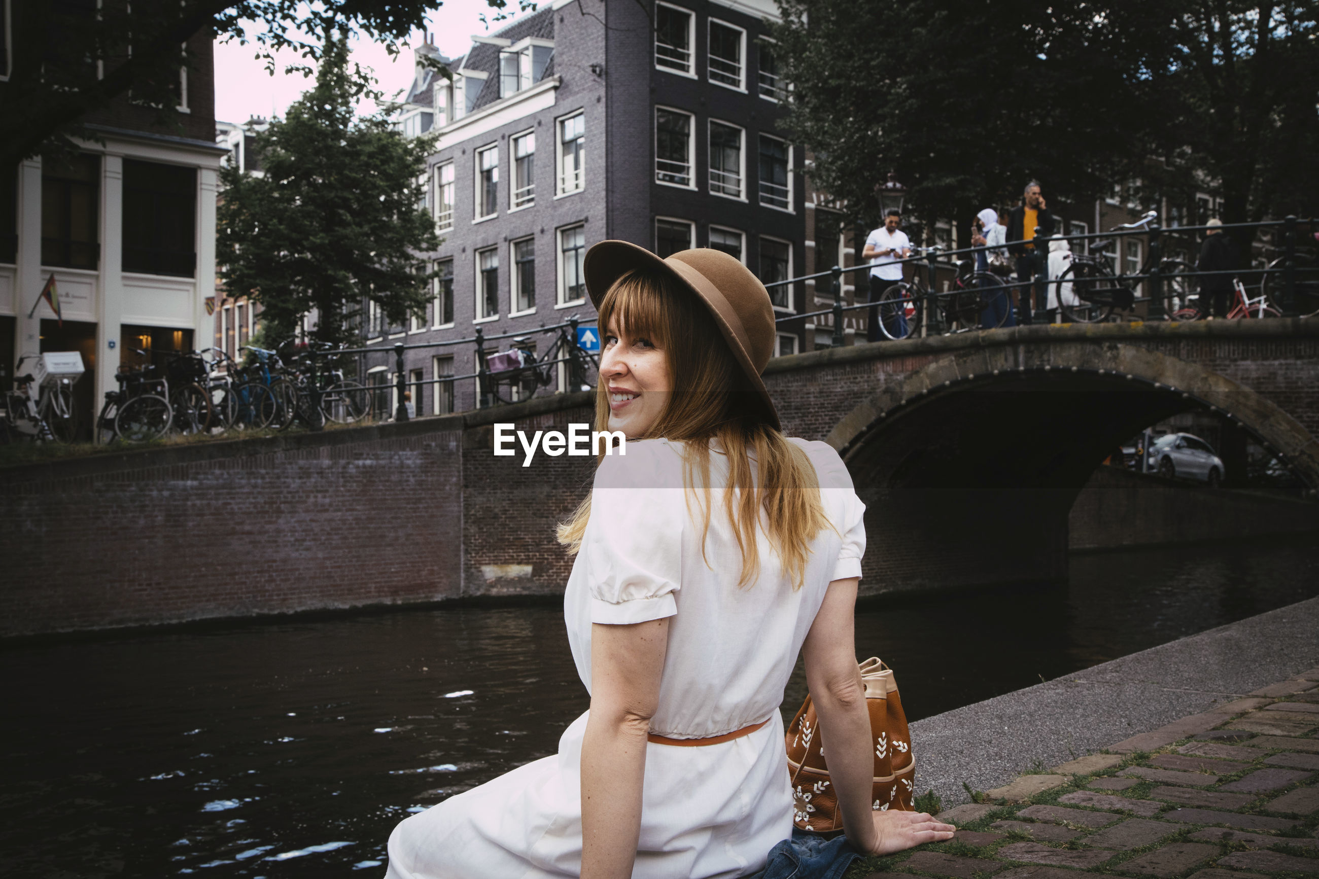 YOUNG WOMAN SMILING IN CANAL AT PARK