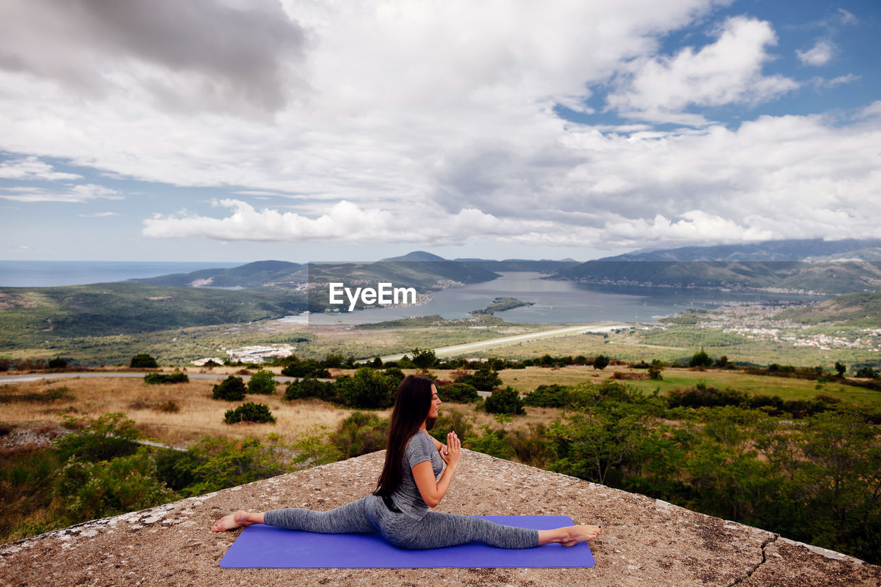 Woman Practicing Yoga Against Cloudy Sky