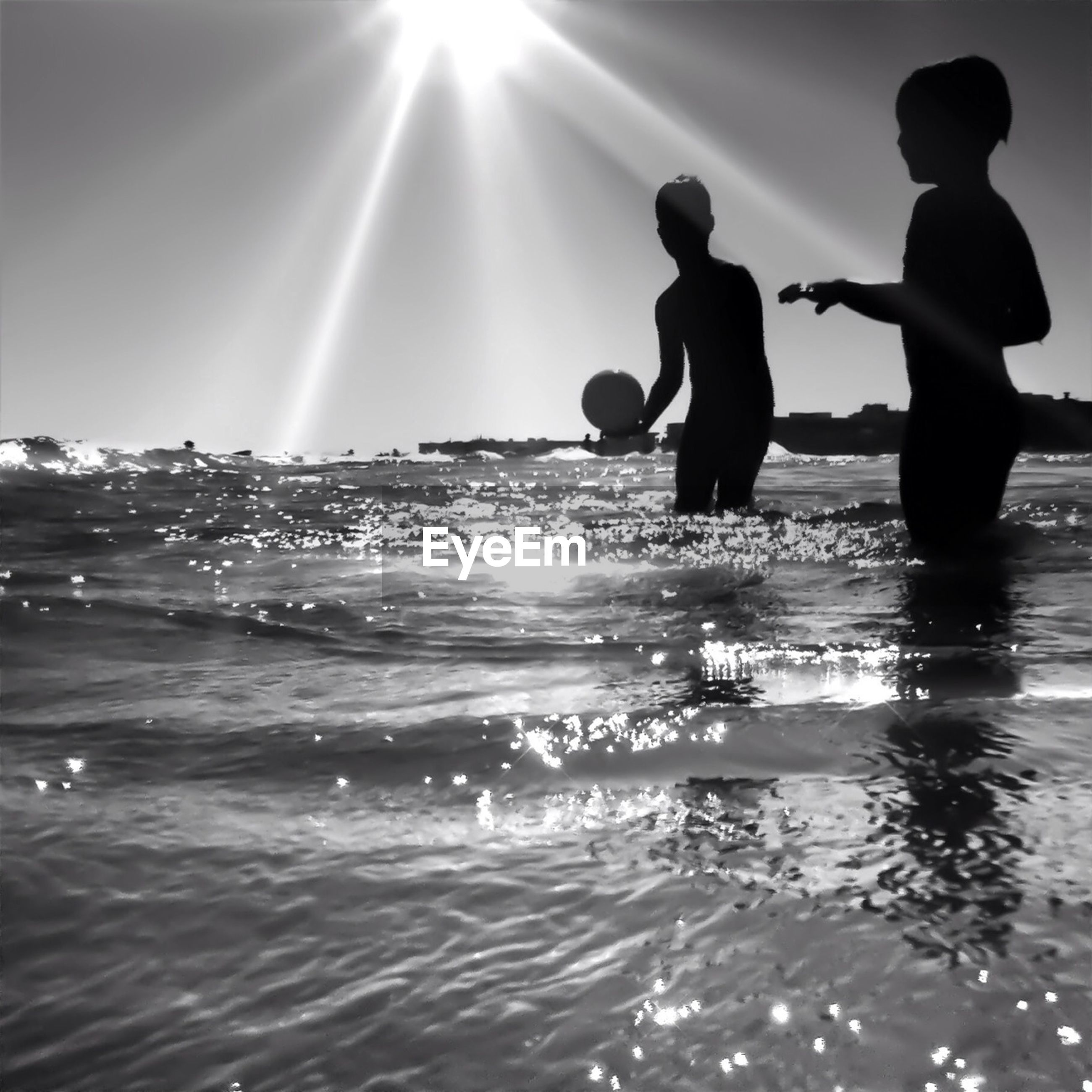 Low angle view of children playing in sea against sky on sunny day