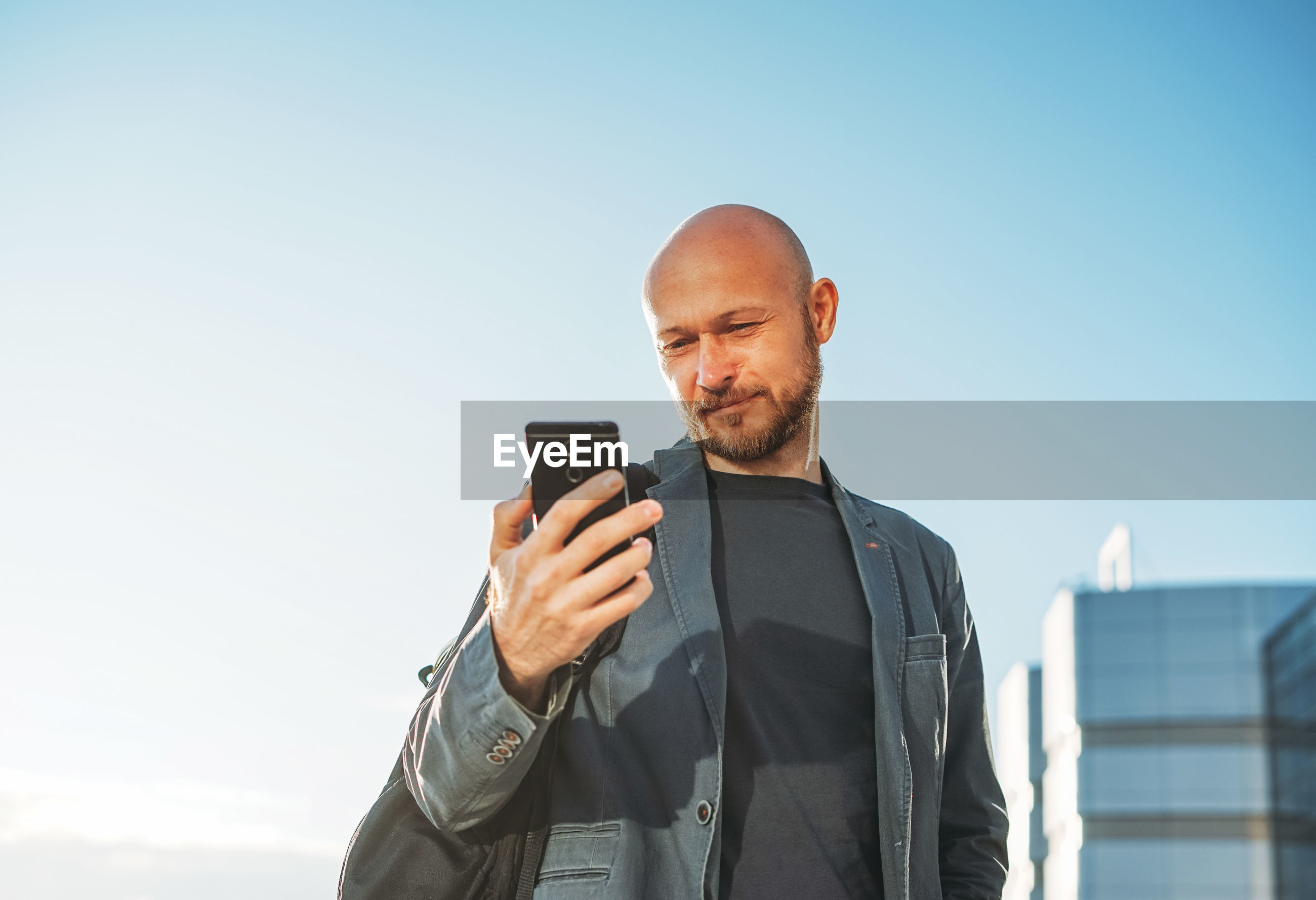 MAN HOLDING SMART PHONE WHILE STANDING ON MOBILE