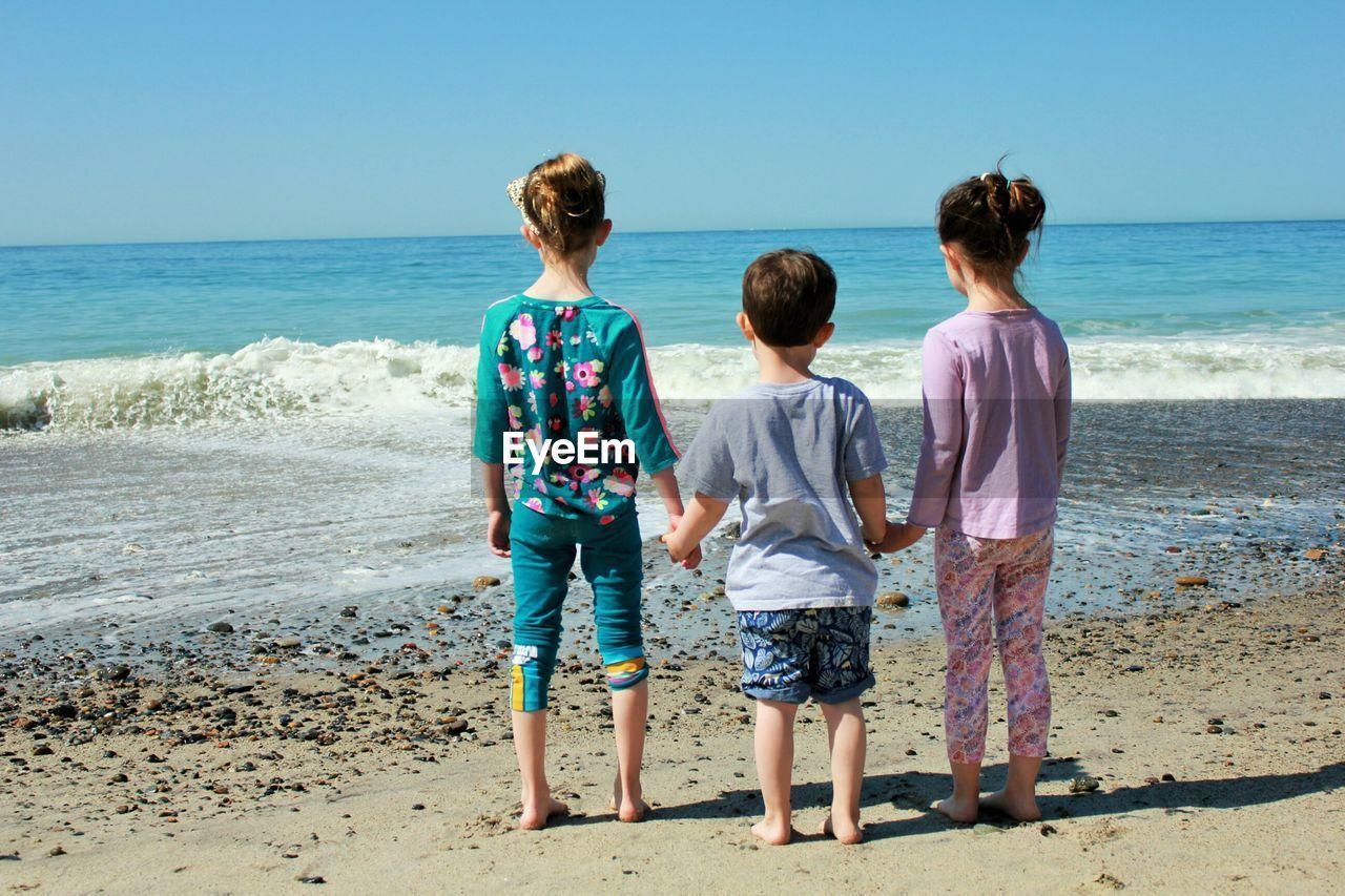 Rear View Of Siblings Standing At Beach Against Sky