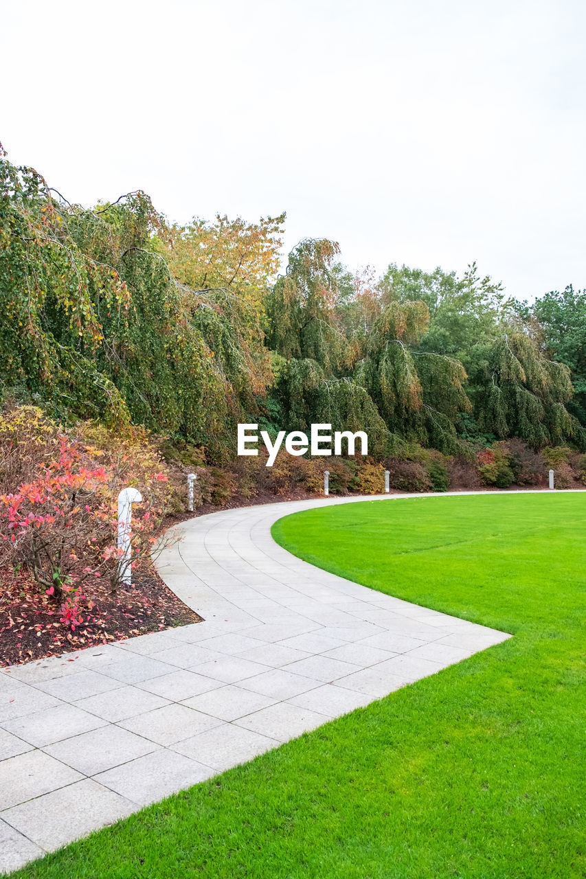 plant, tree, grass, green color, sky, nature, no people, growth, day, beauty in nature, tranquility, footpath, park, tranquil scene, scenics - nature, clear sky, outdoors, land, park - man made space, landscape, garden path, ornamental garden, flowerbed