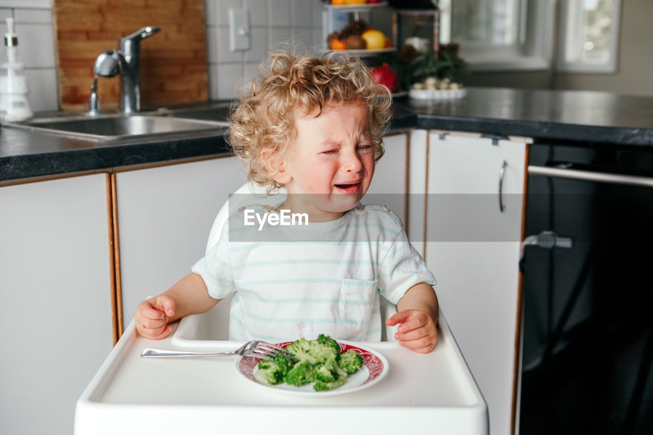 Crying caucasian kid boy with broccoli on plate.  toddler screaming in tantrum. terrible two.
