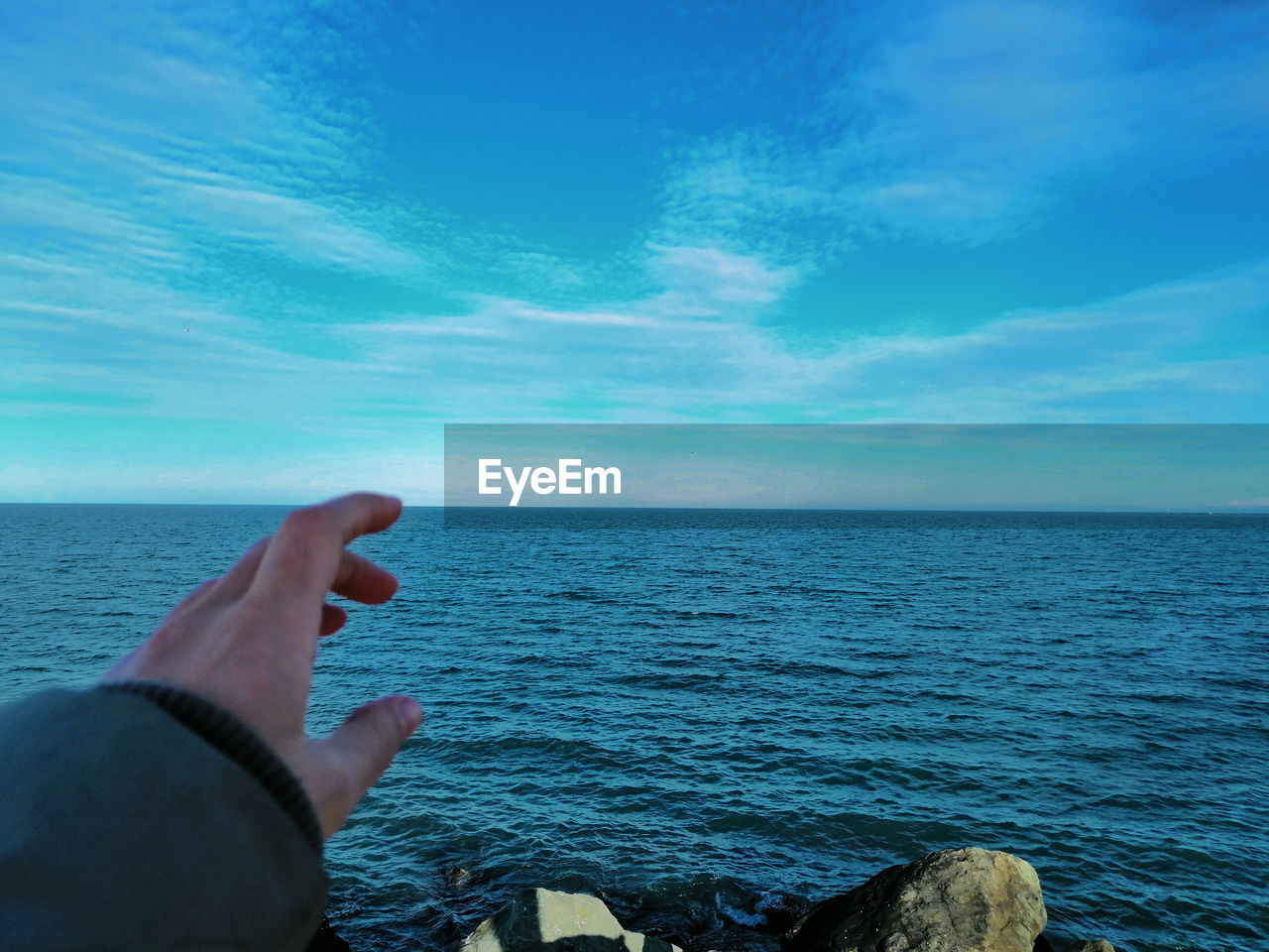 MIDSECTION OF PERSON HAND BY SEA AGAINST SKY