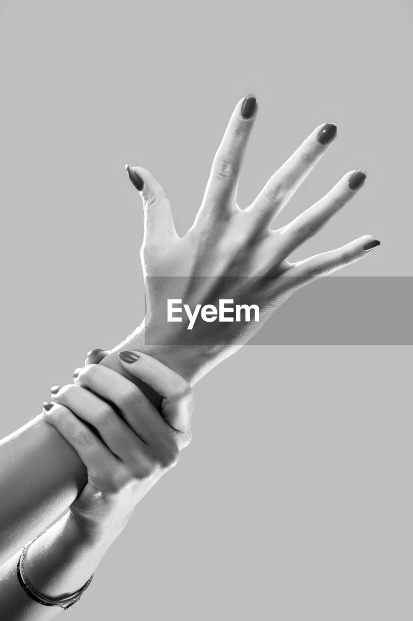 Close-up of hand touching finger against black background