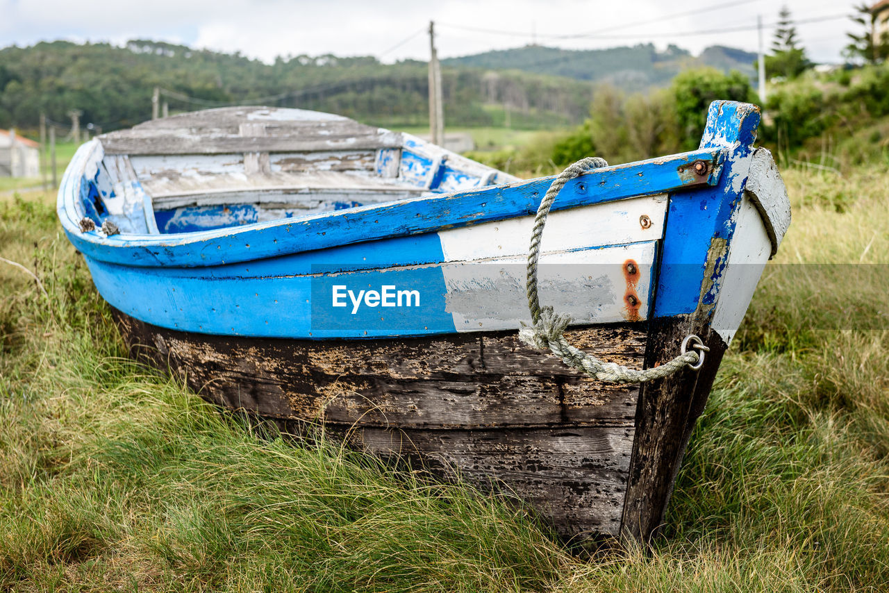 land, grass, field, nautical vessel, nature, plant, day, transportation, no people, wood - material, water, mode of transportation, blue, tranquility, outdoors, moored, tranquil scene, focus on foreground, old, rowboat, fishing boat