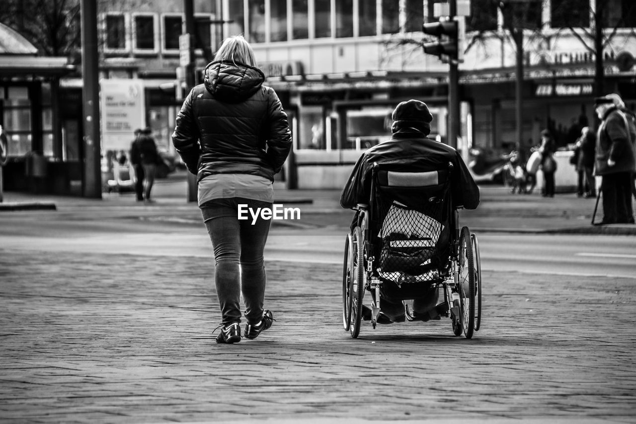 Rear View Of Woman Walking By Man On Wheelchair At Walkway