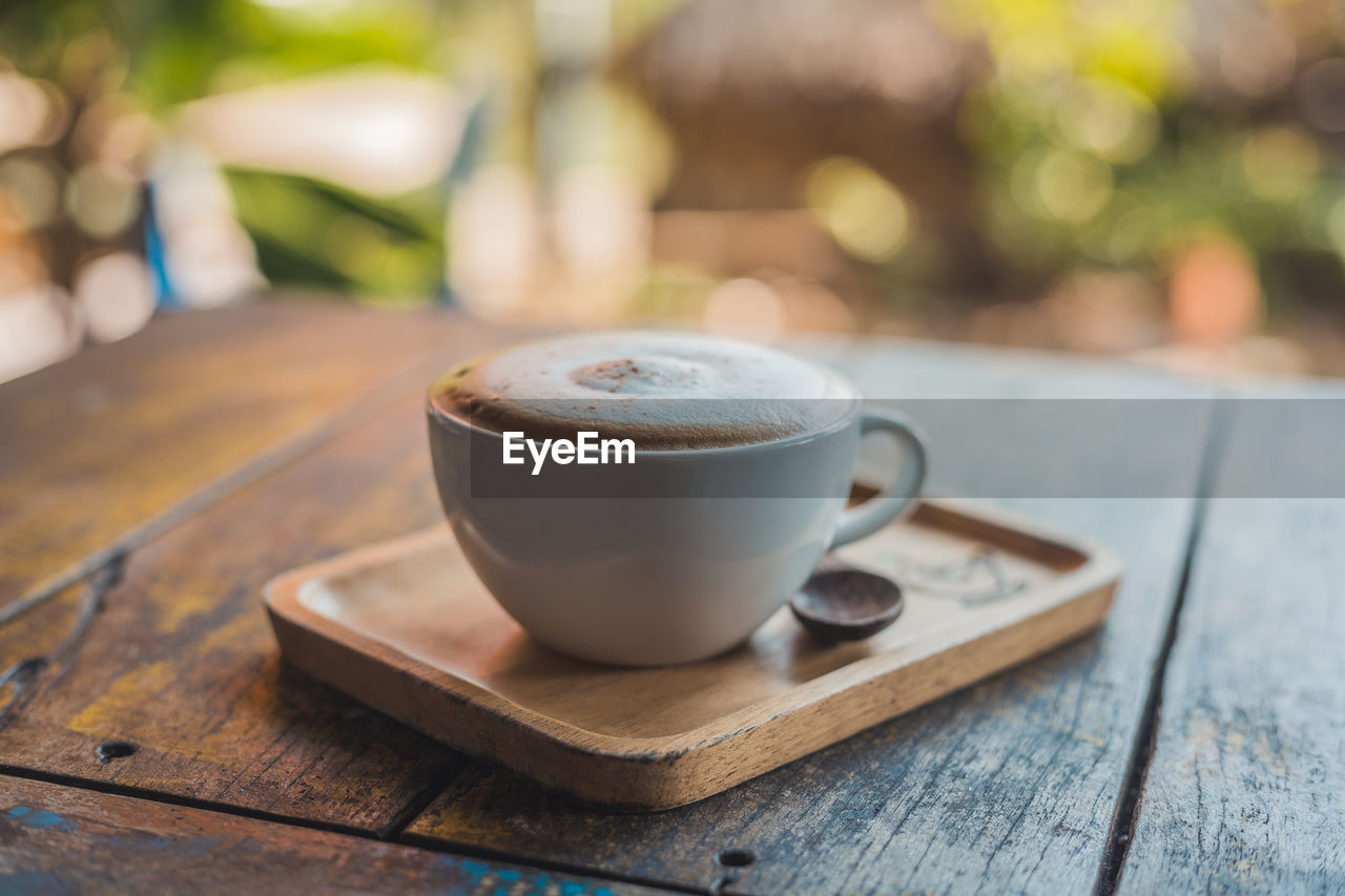 wood - material, food and drink, cup, coffee, mug, coffee cup, table, coffee - drink, focus on foreground, drink, still life, refreshment, spoon, eating utensil, close-up, saucer, kitchen utensil, no people, crockery, freshness, hot drink, frothy drink, non-alcoholic beverage, latte, temptation