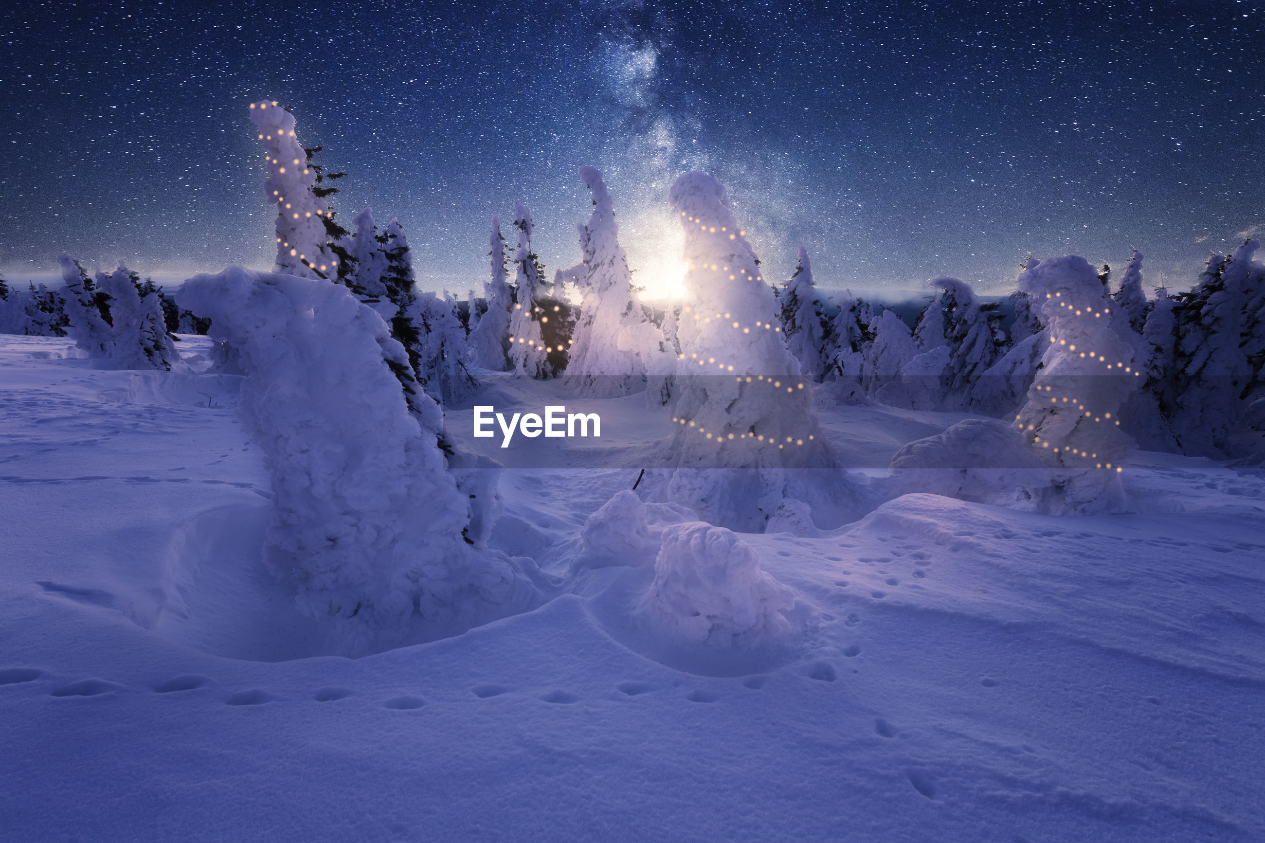 Scenic view of snowcapped field against sky at night