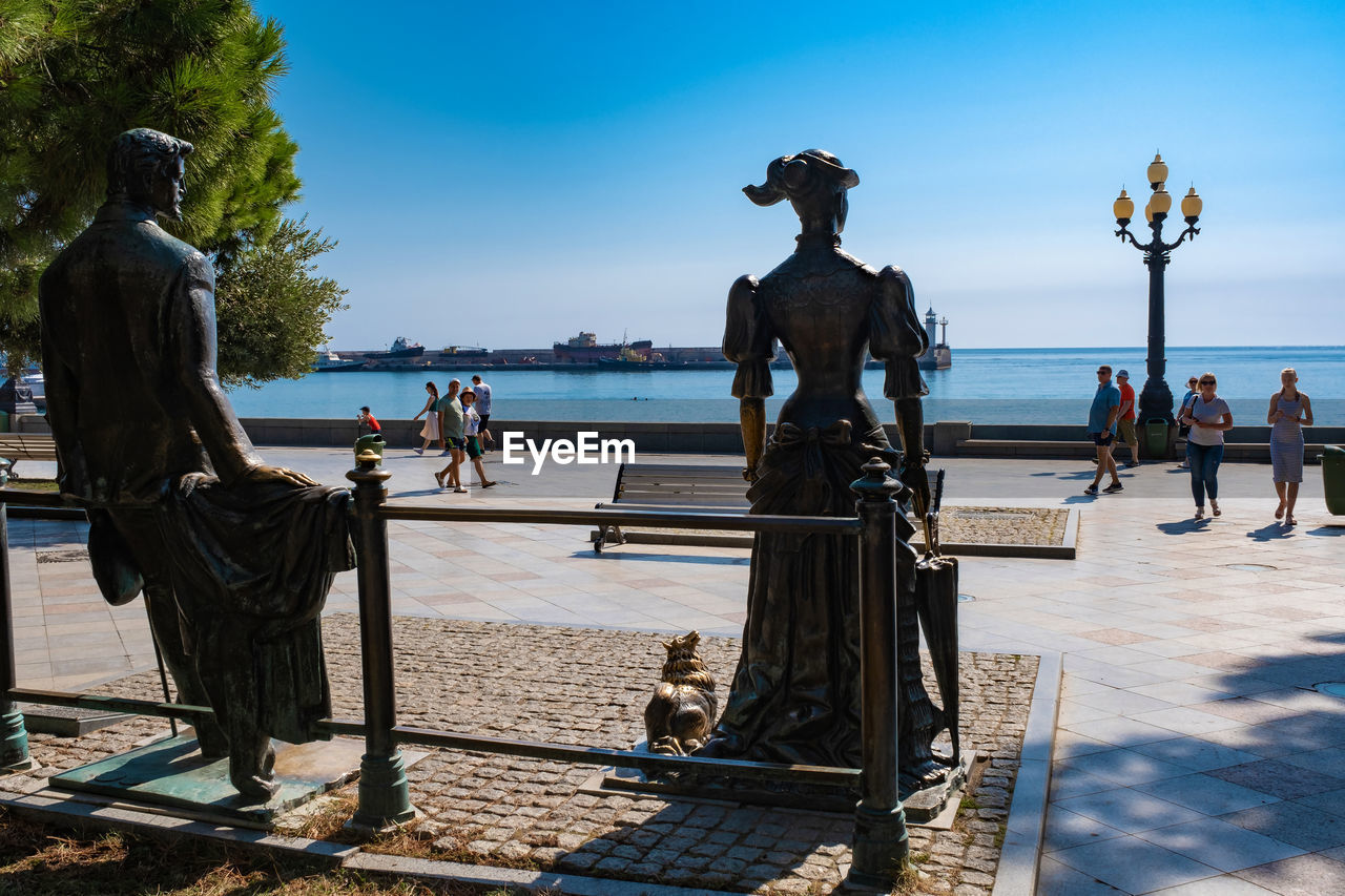 water, sky, sea, nature, beach, group of people, sculpture, representation, art and craft, day, statue, real people, men, sunlight, human representation, women, people, railing, horizon over water, outdoors